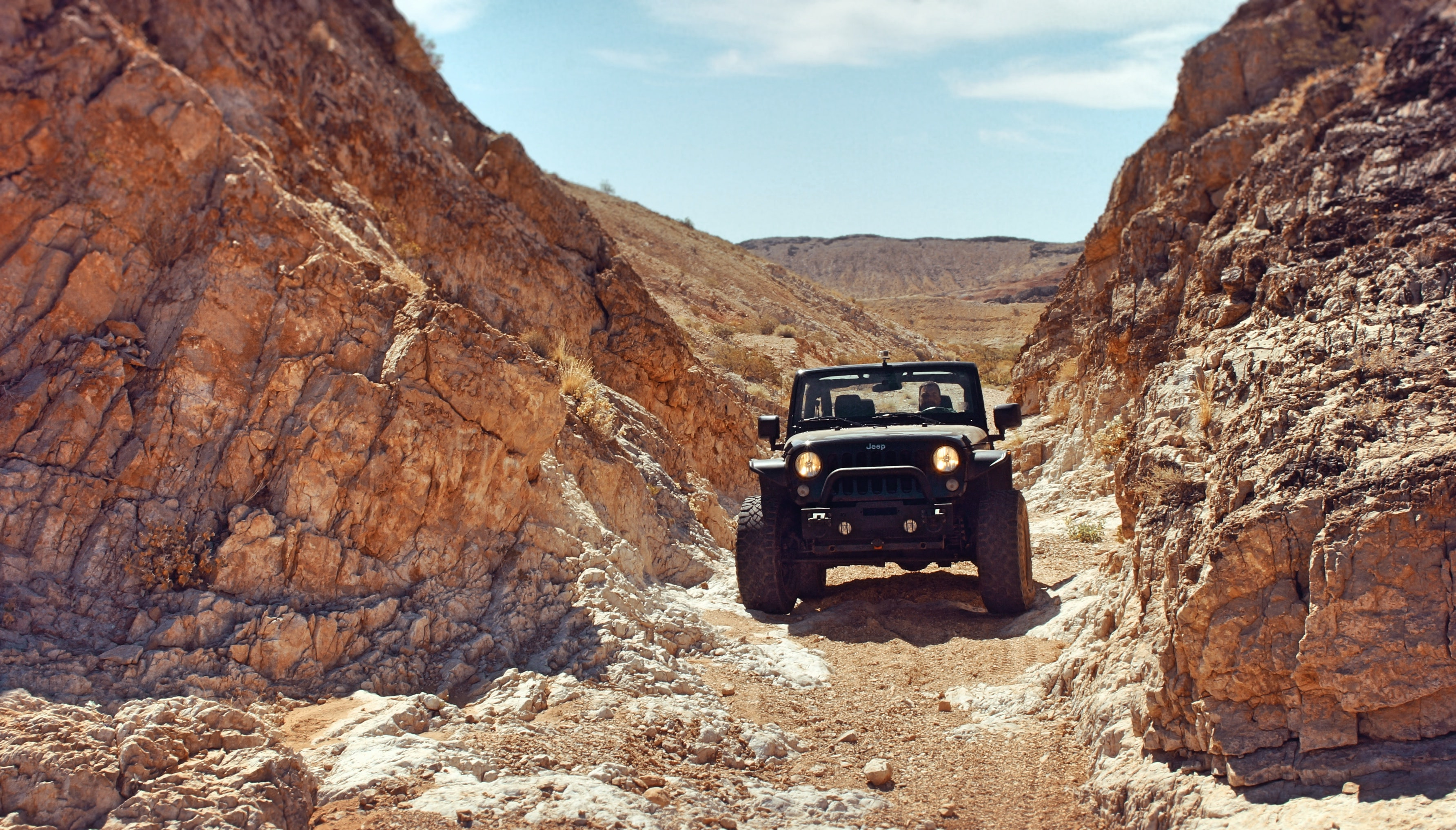 Jeep truck drives through rough terrains in a desert canyon in Nevada