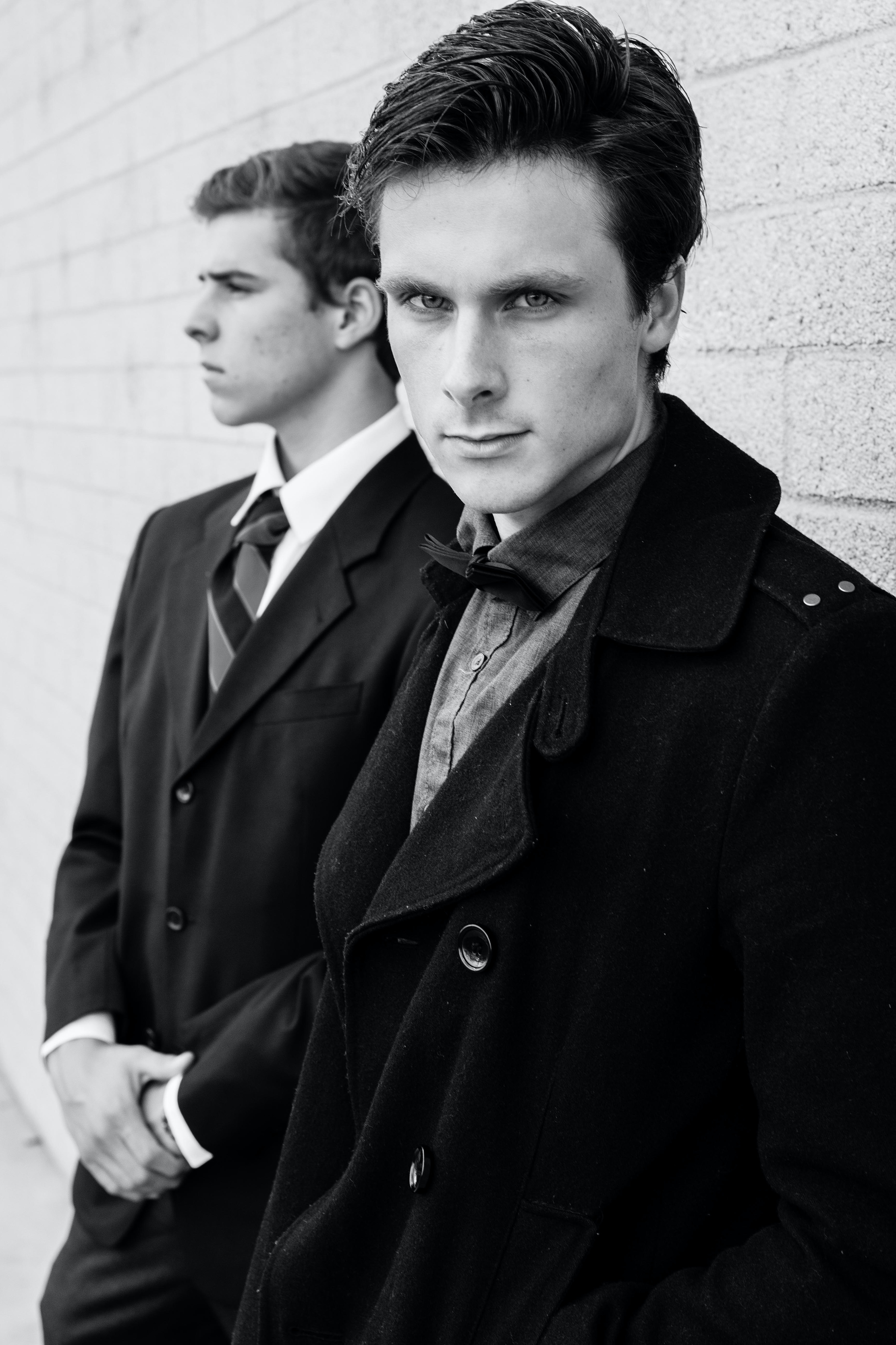 A black-and-white shot of two young men in formal attire near a wall