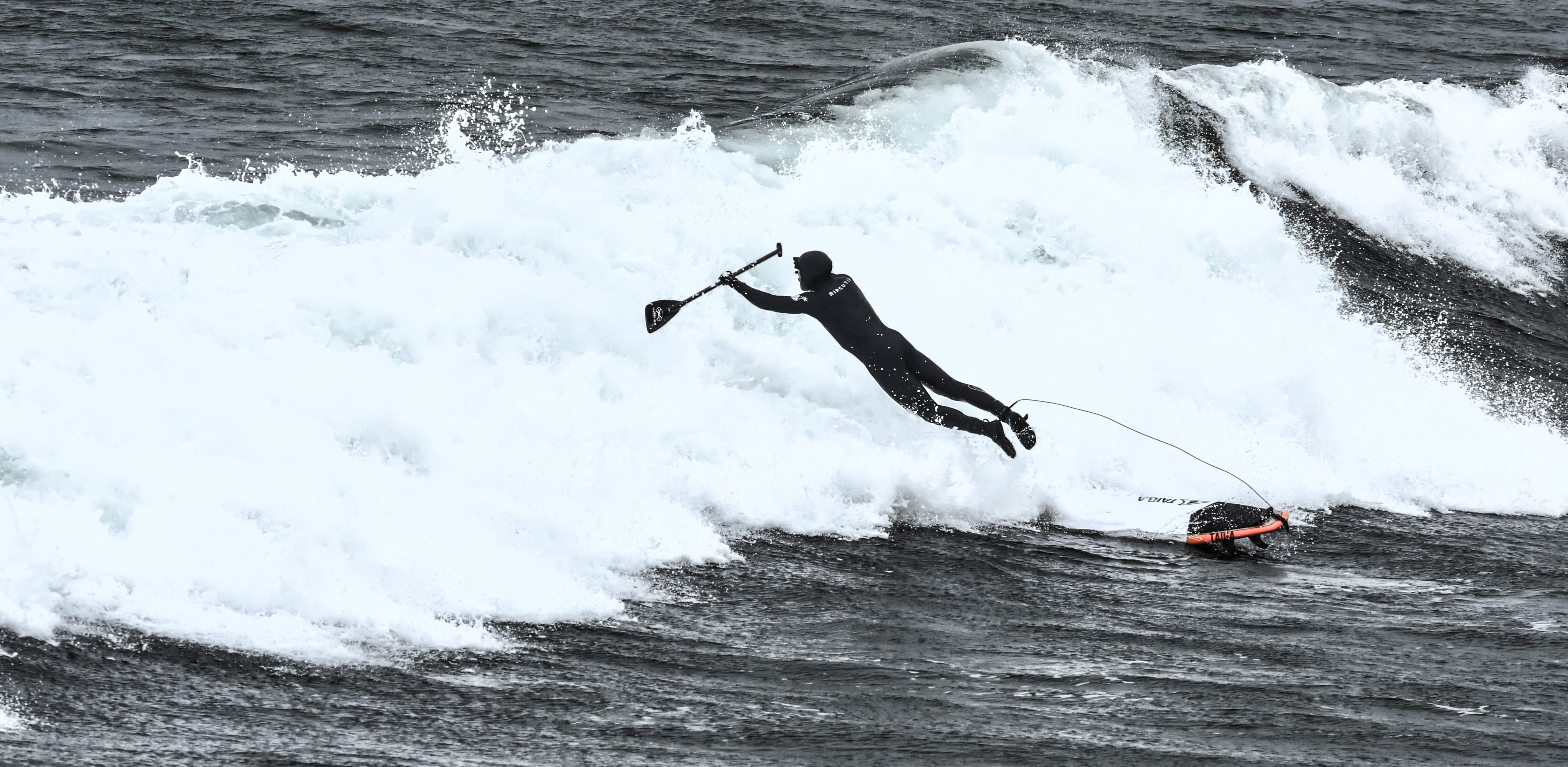 A man in a wetsuit, holding a paddle, jumping or falling off a paddleboard as a wave hits, at Wells