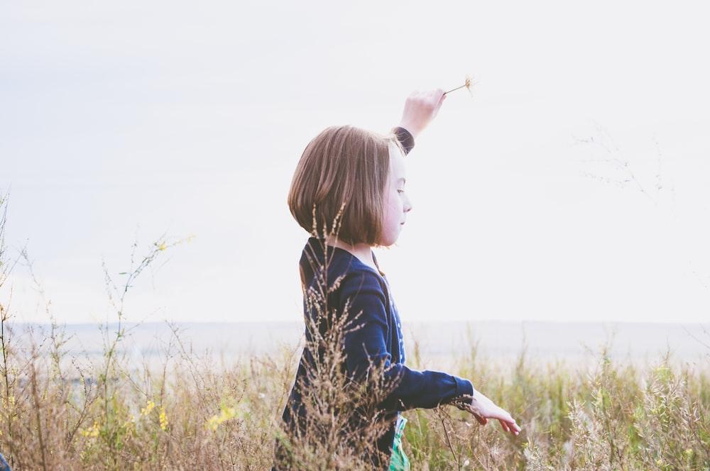 girl on grass field under white sky