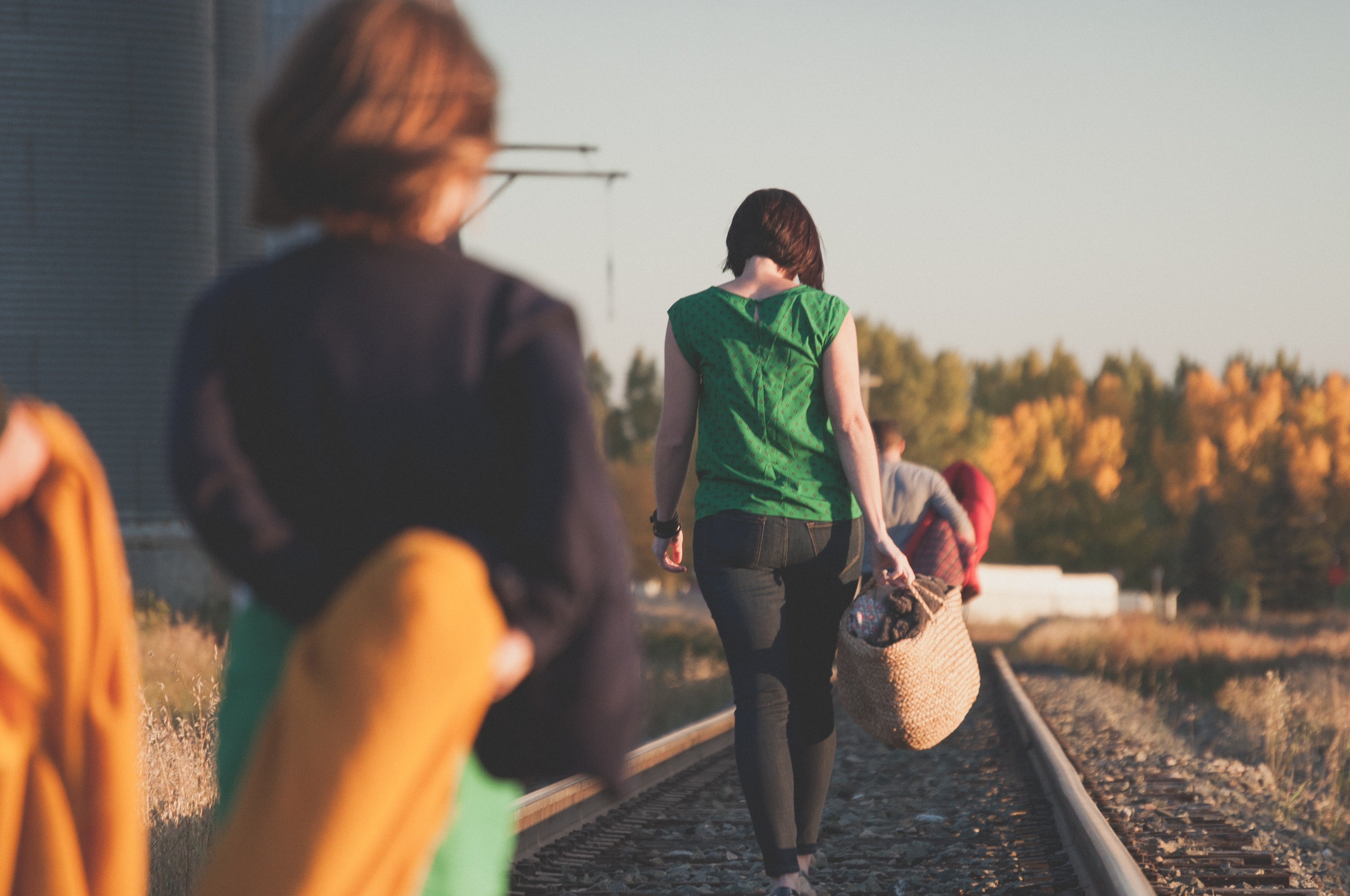 A woman in green walks along the railroad track behind a man and is followed by a child.