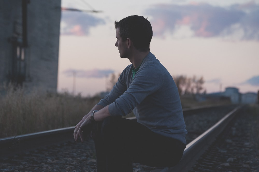 man sitting on railway under gray sky