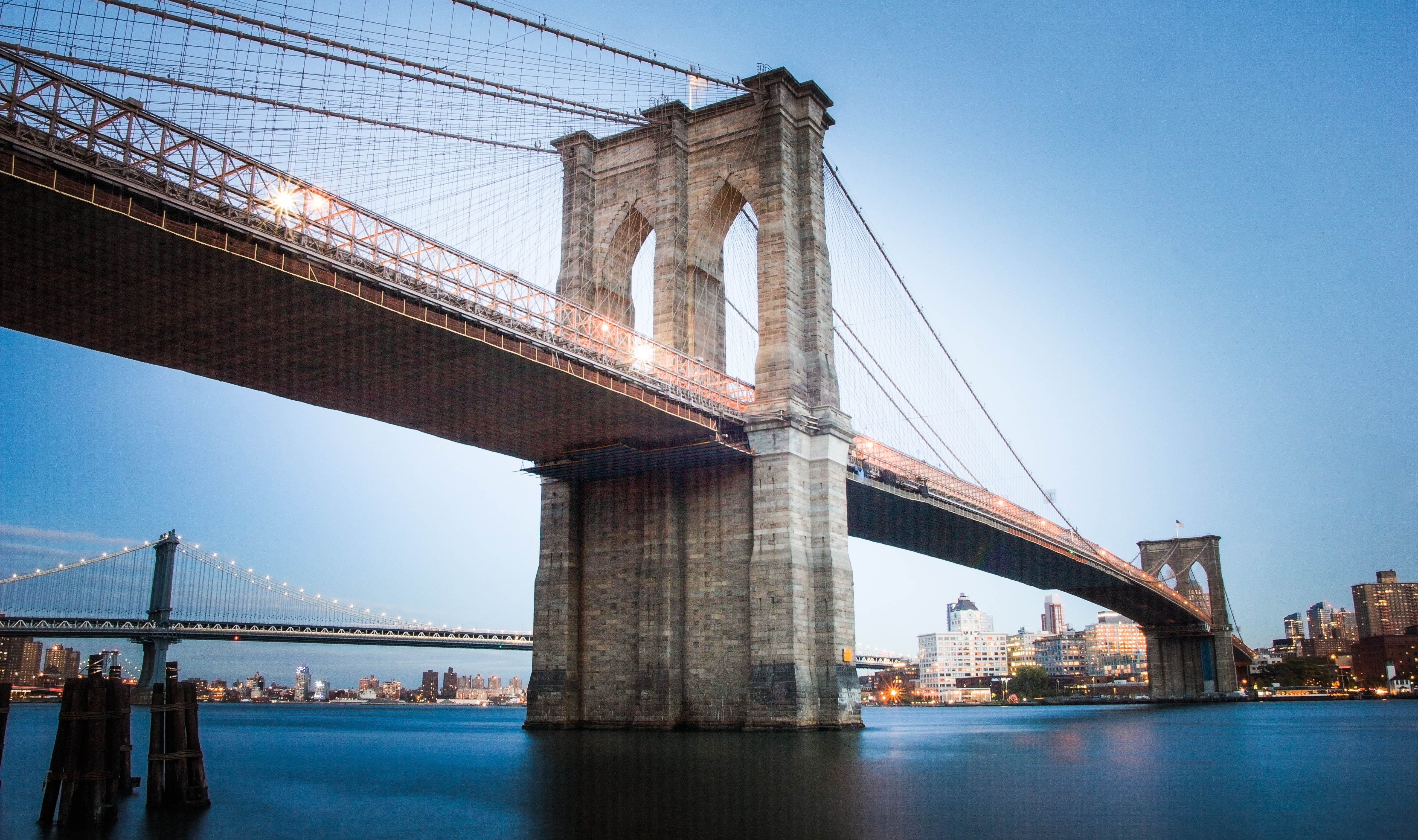 The Brooklyn Bridge with the Brooklyn skyline in the distance in New York City