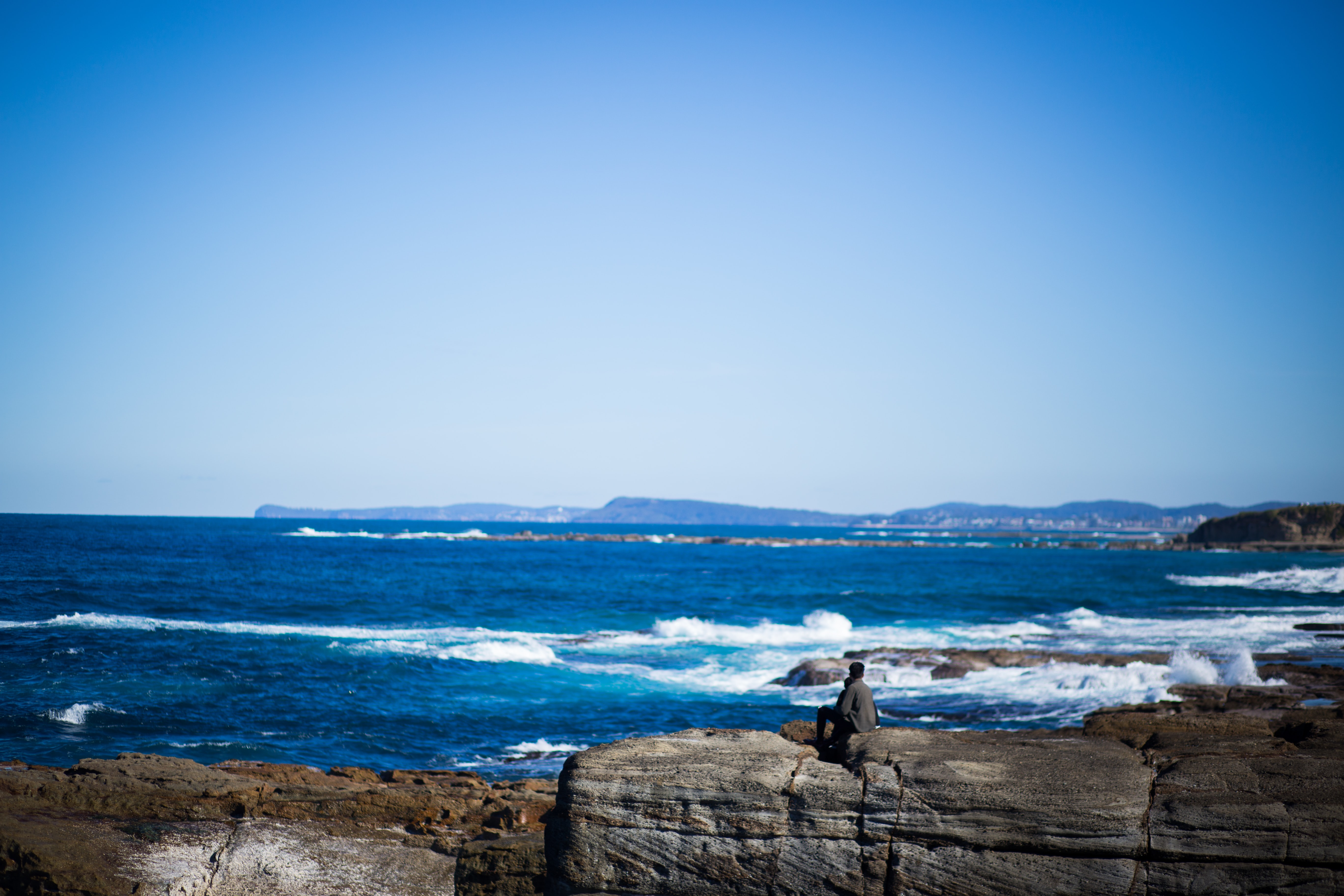 man seats on brown stone near sea during daytime