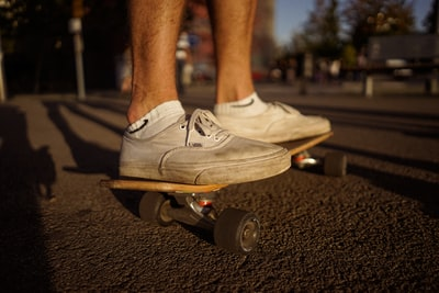 person on top of skateboard on gray pavement skate zoom background