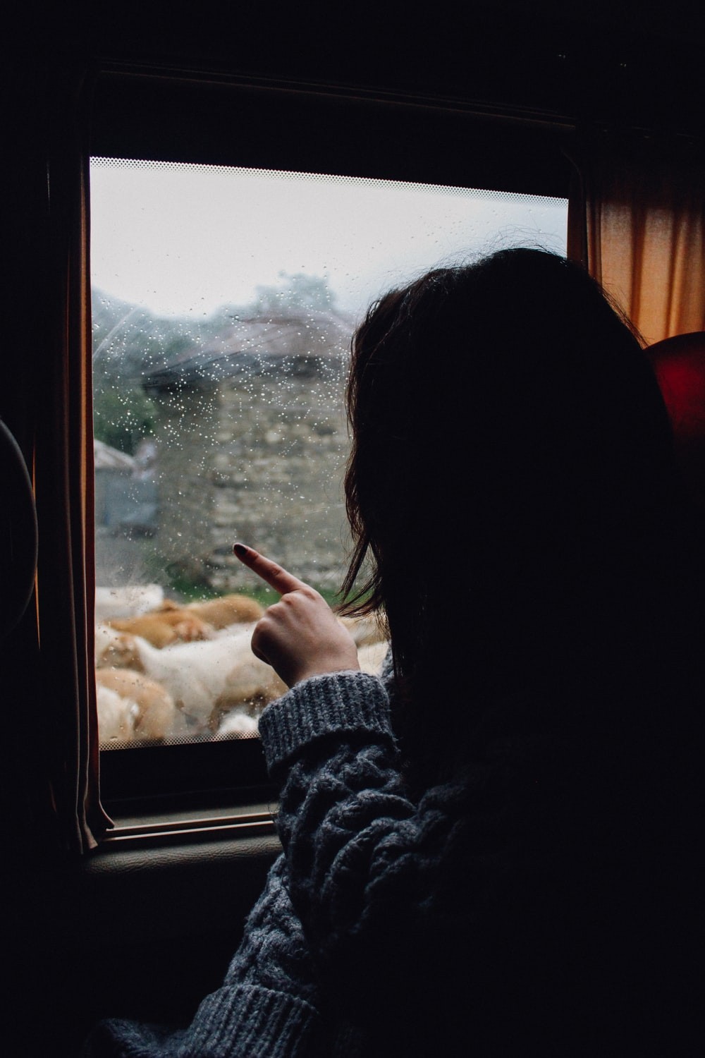 woman in gray knitted sweater looking and pointing at the window