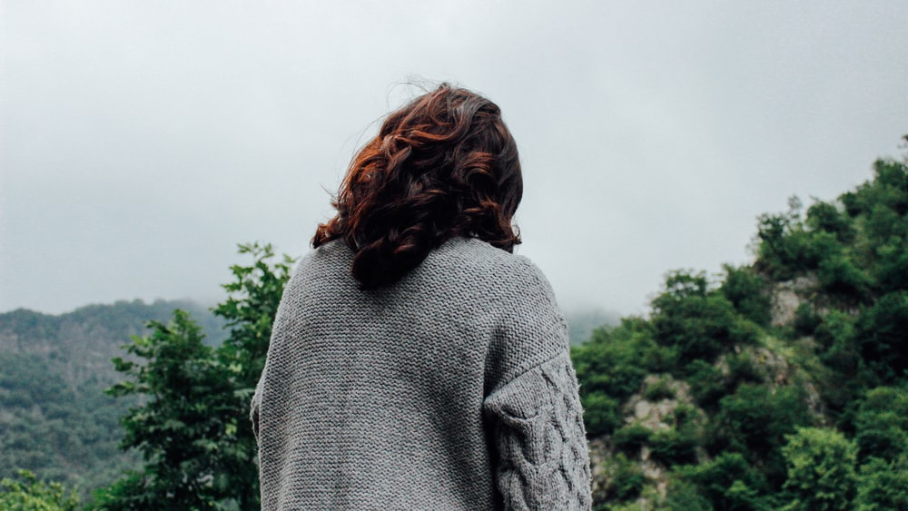 woman in gray sweater standing in front of trees during daytime