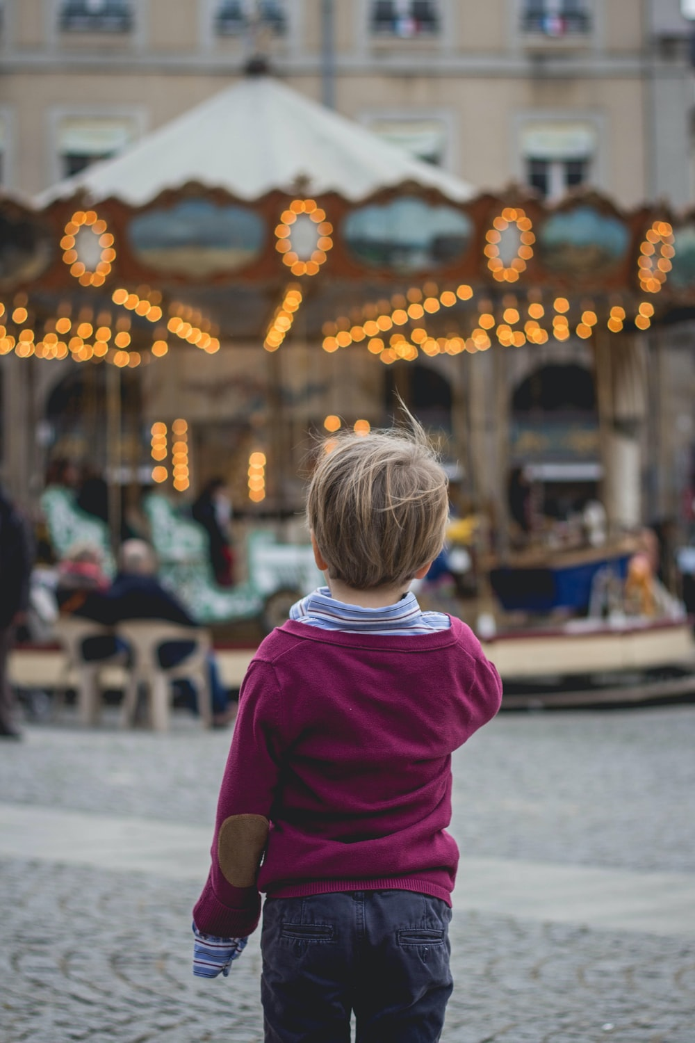selective focus photography of boy standing in front of carousel
