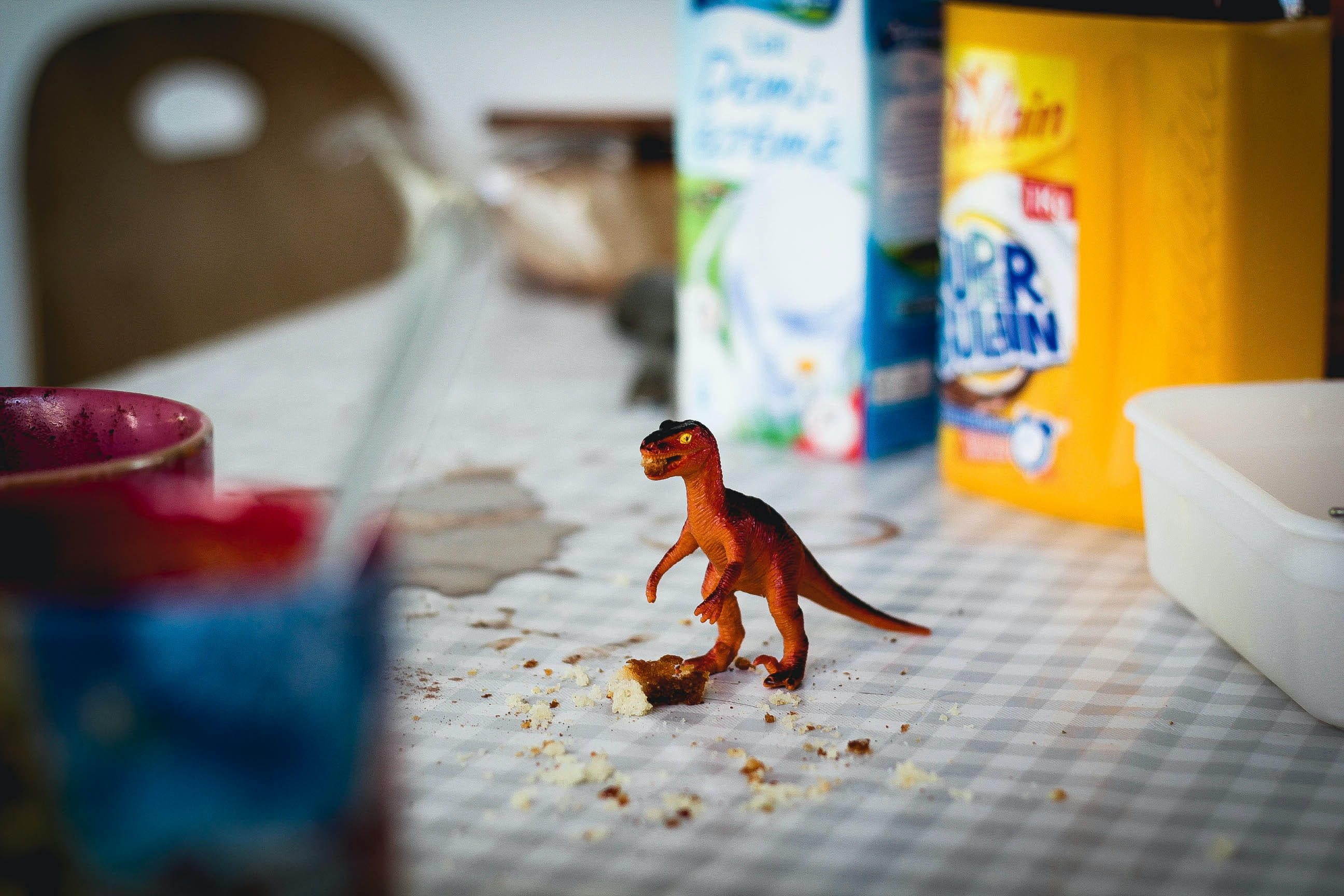 A little toy dinosaur on the kitchen table.