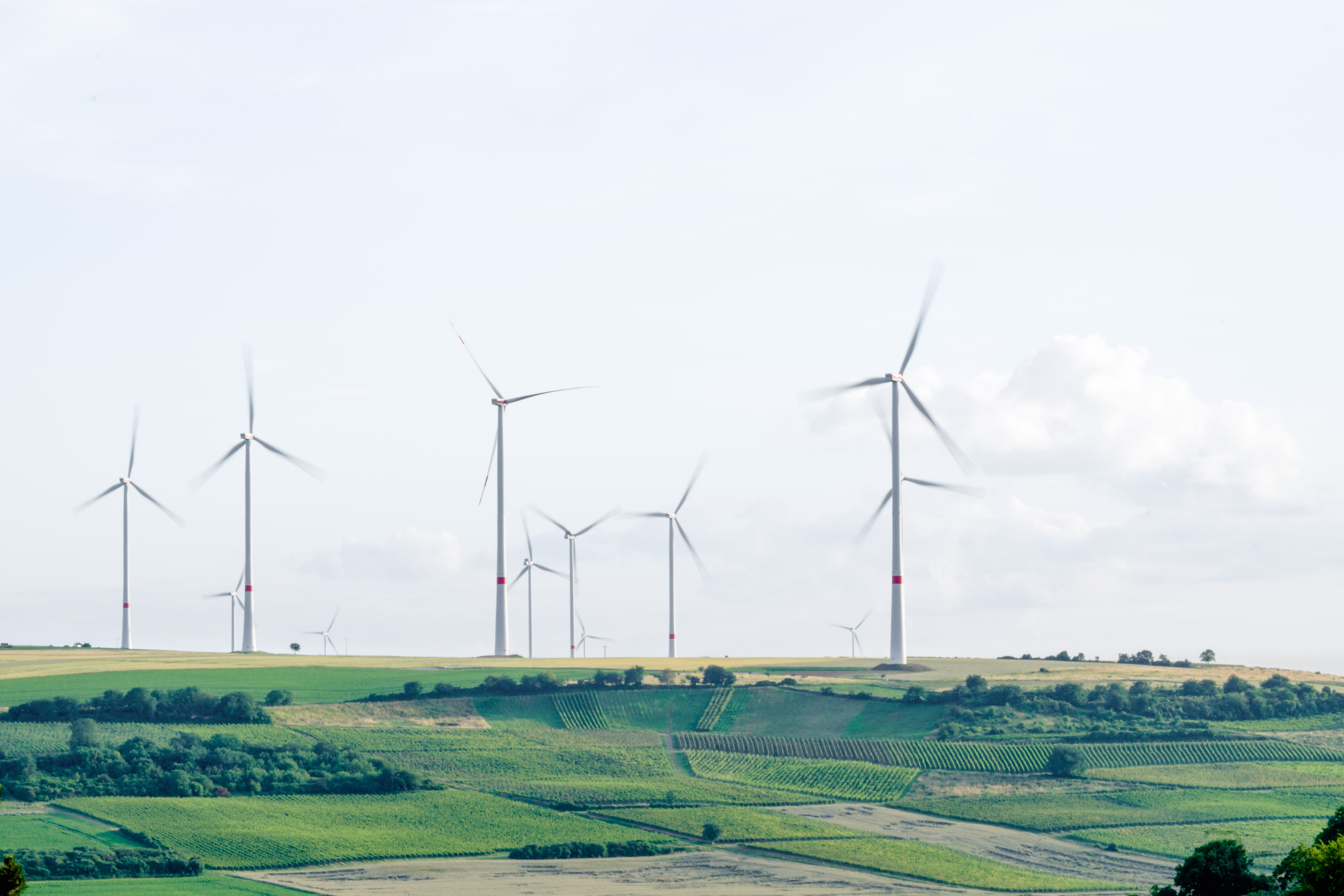 A group of wind turbines in a hilly landscape.