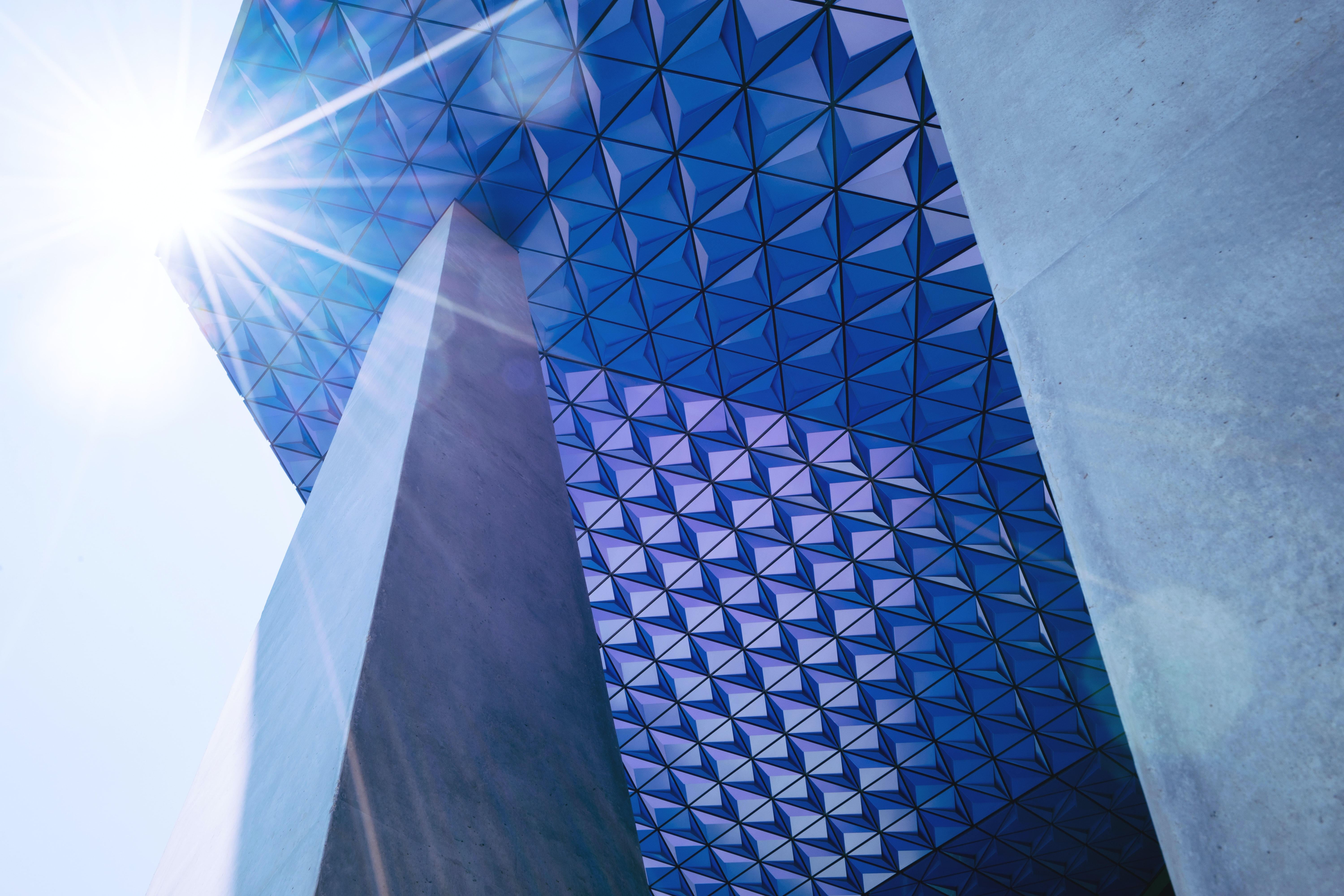 A lens flare over an overhang in the facade of a modern building