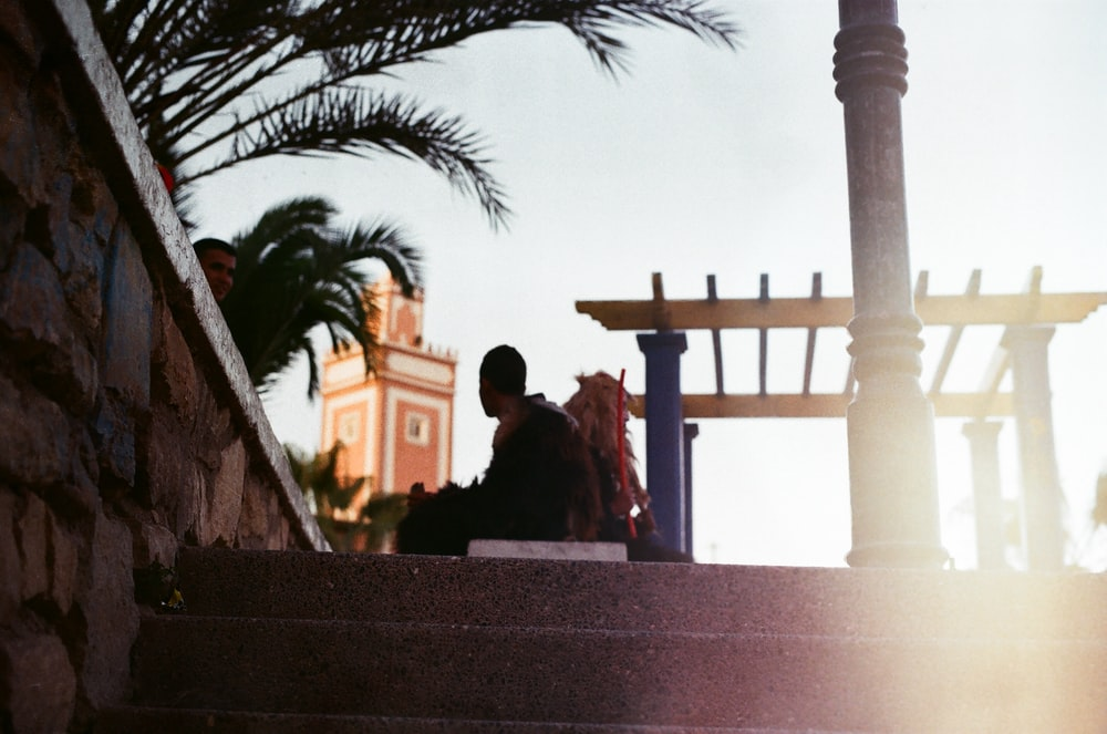 photography of silhouette of man sitting on park bench near concrete stairs