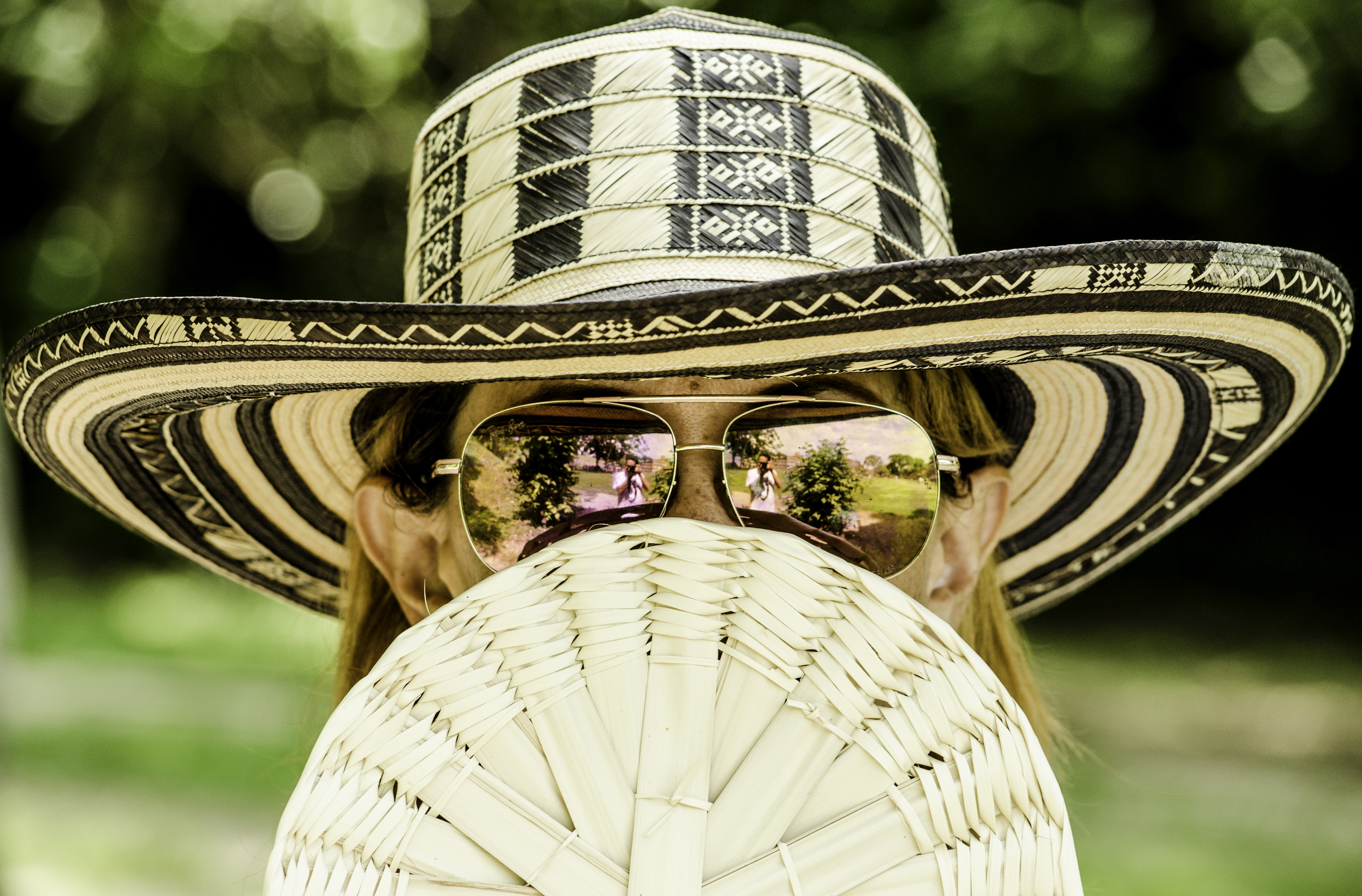 A blonde woman wearing a sun hat with sunglasses while holding a fan