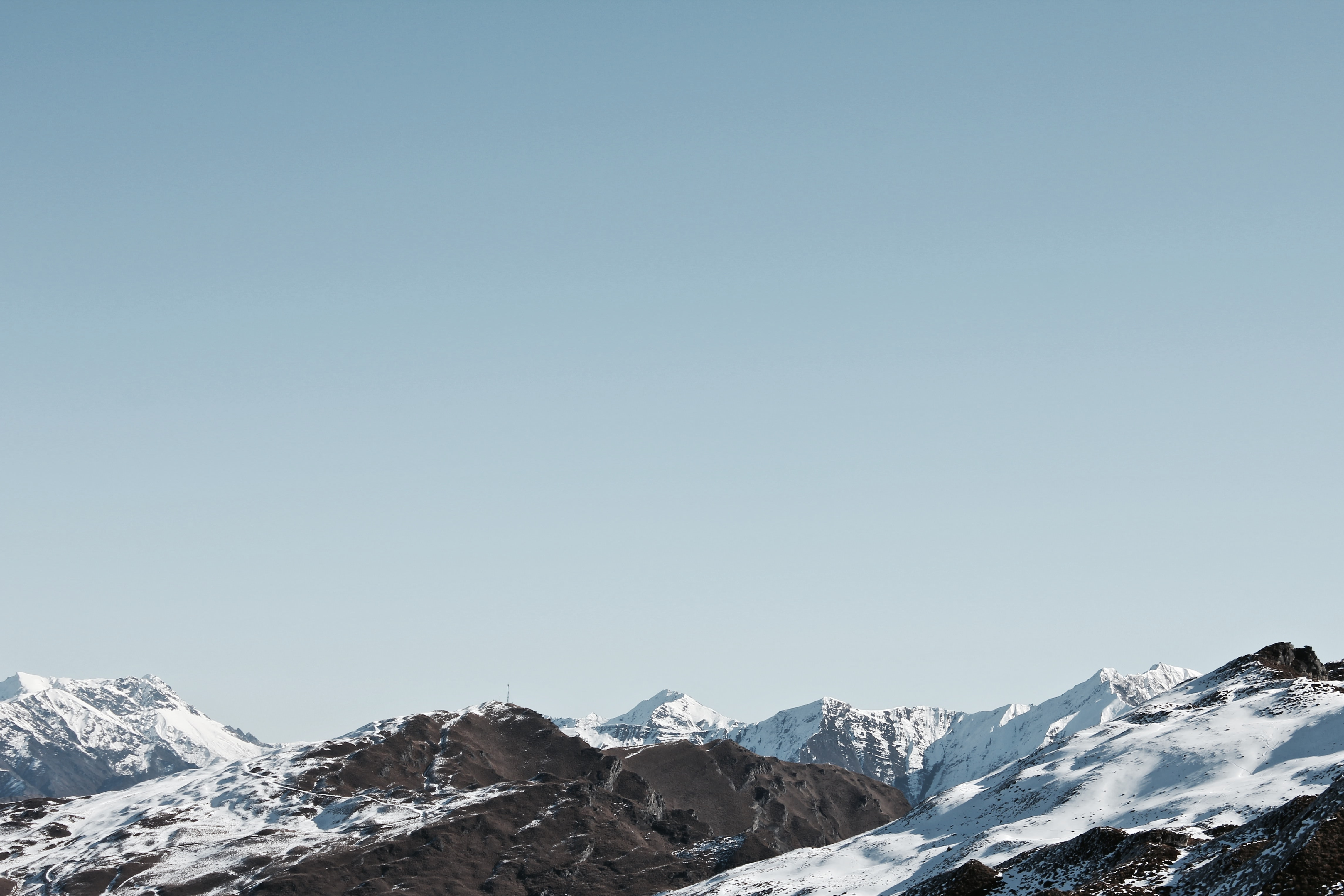 A mountain range dusted with snow under a pale blue sky