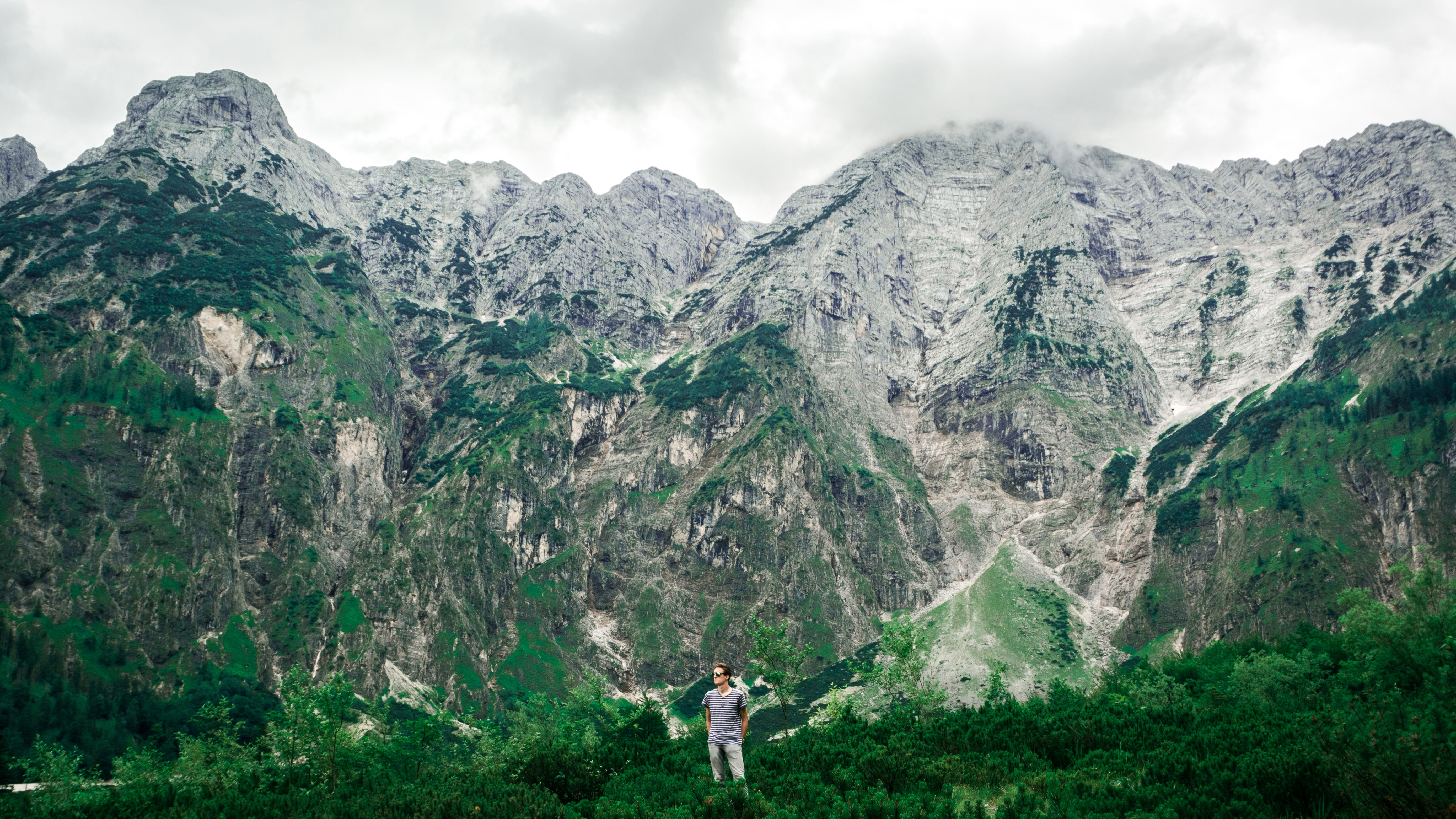 man standing near mountains surrounded with trees
