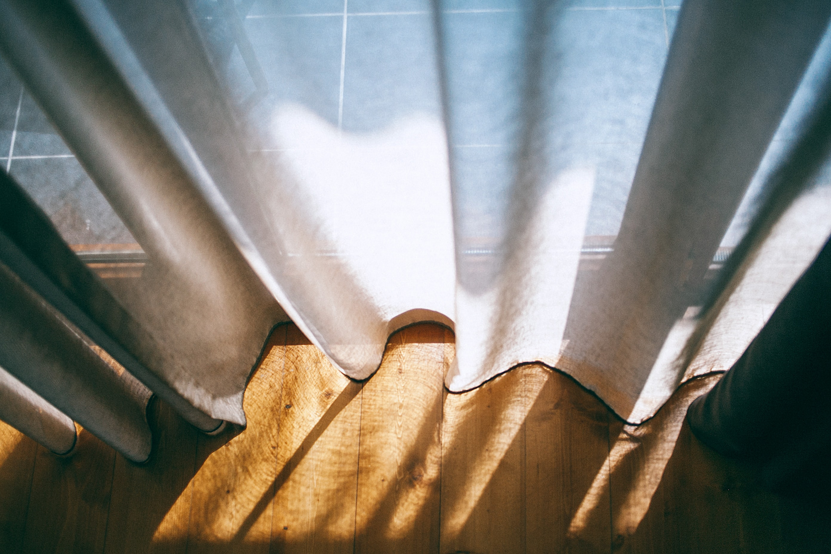 The sunlight is coming through the windows with white curtains in Tbilisi.