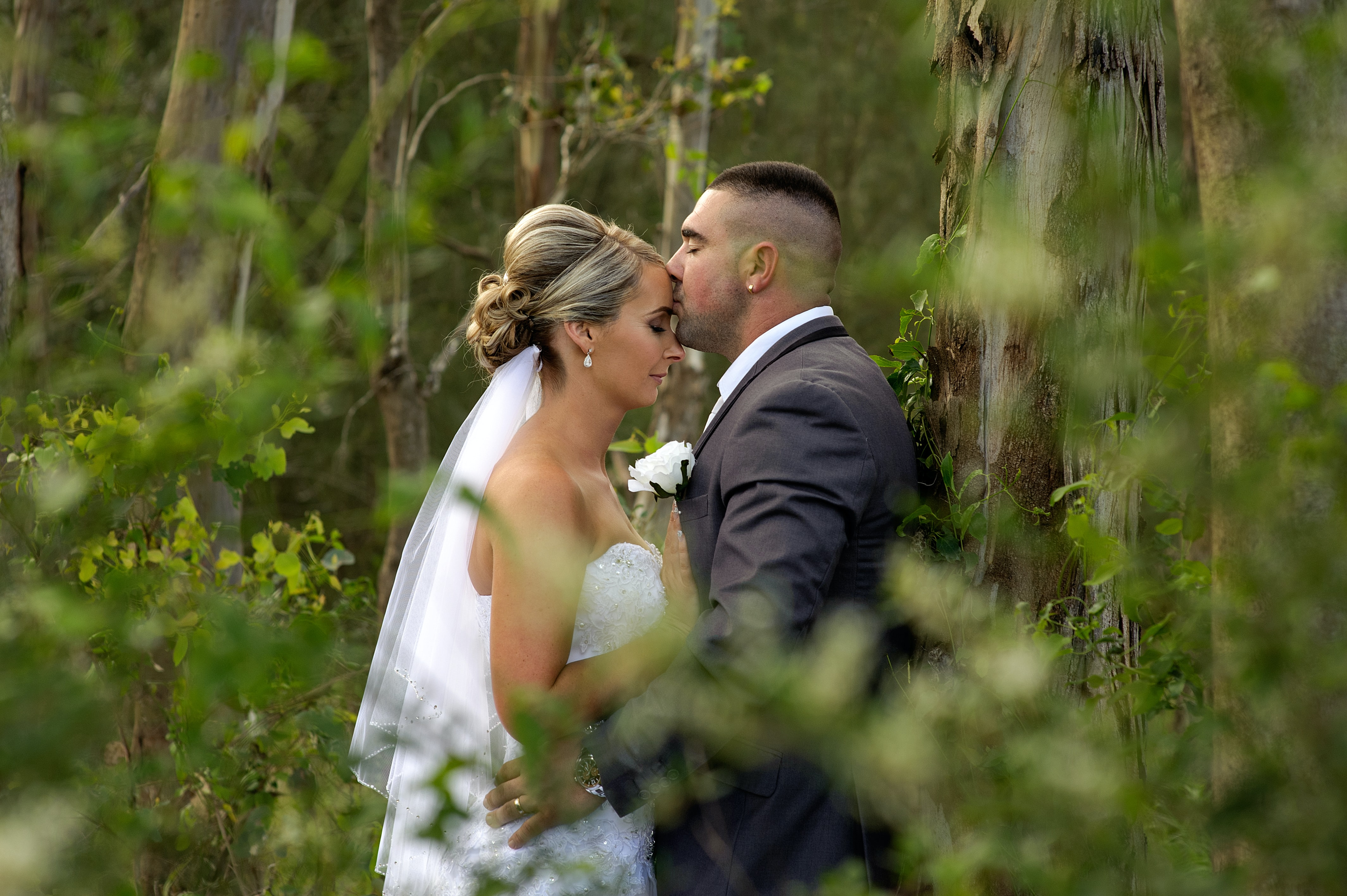 A man kisses a woman's forehead in a forest of trees on their wedding day