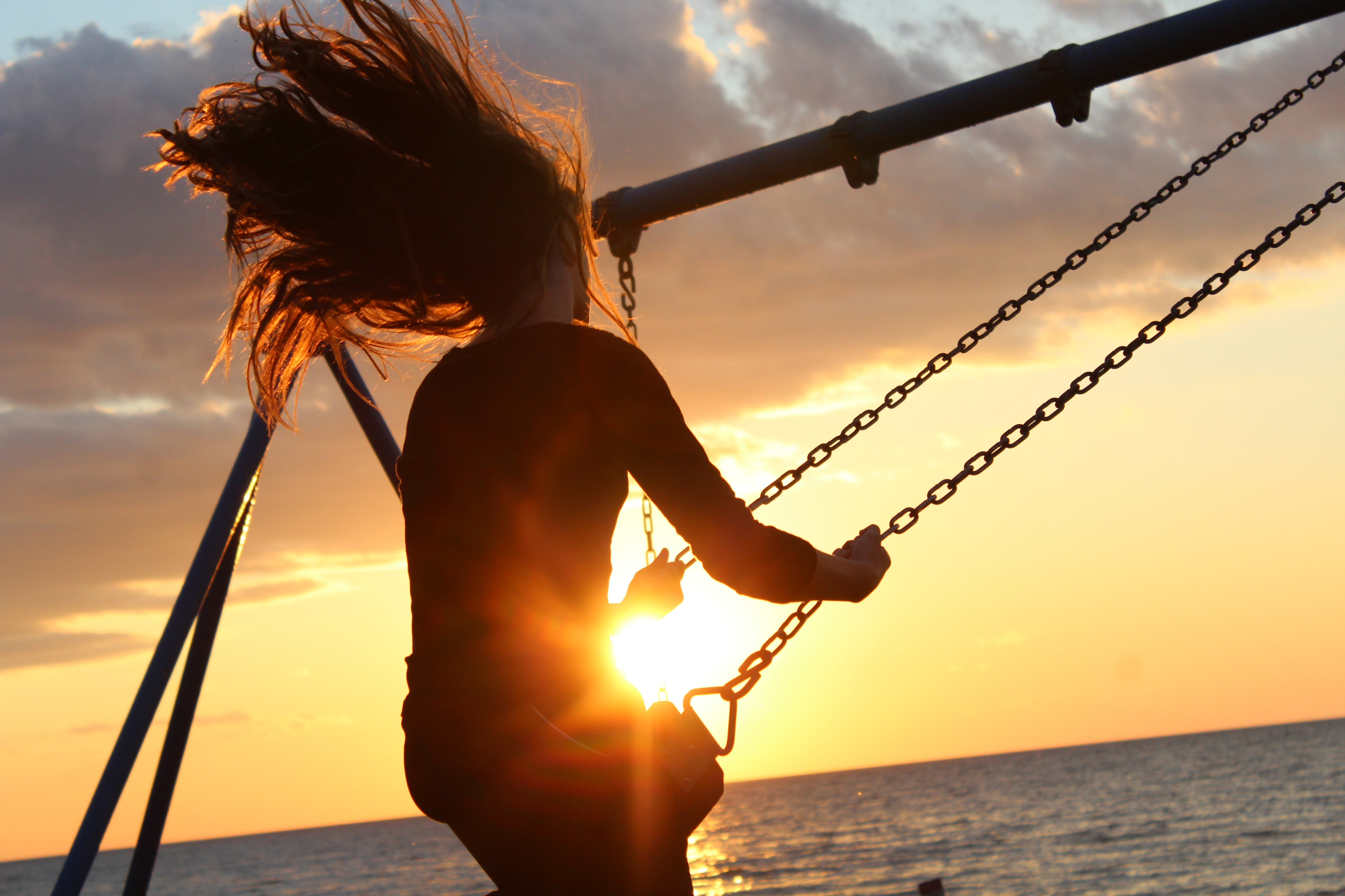 A woman with long hair swings high on a swing near the ocean at sunset.