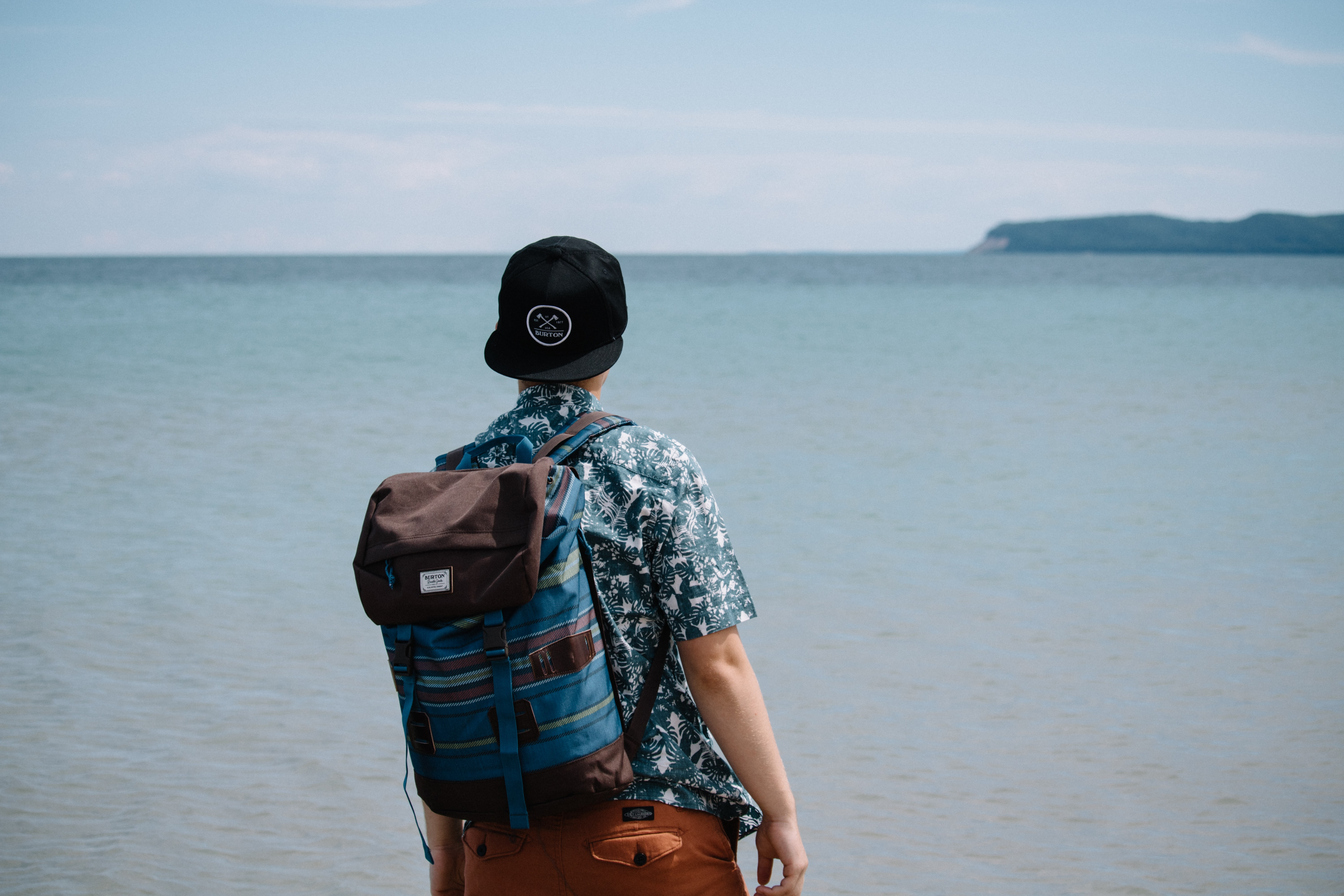A male backpacker in a black hat looking off into the sea