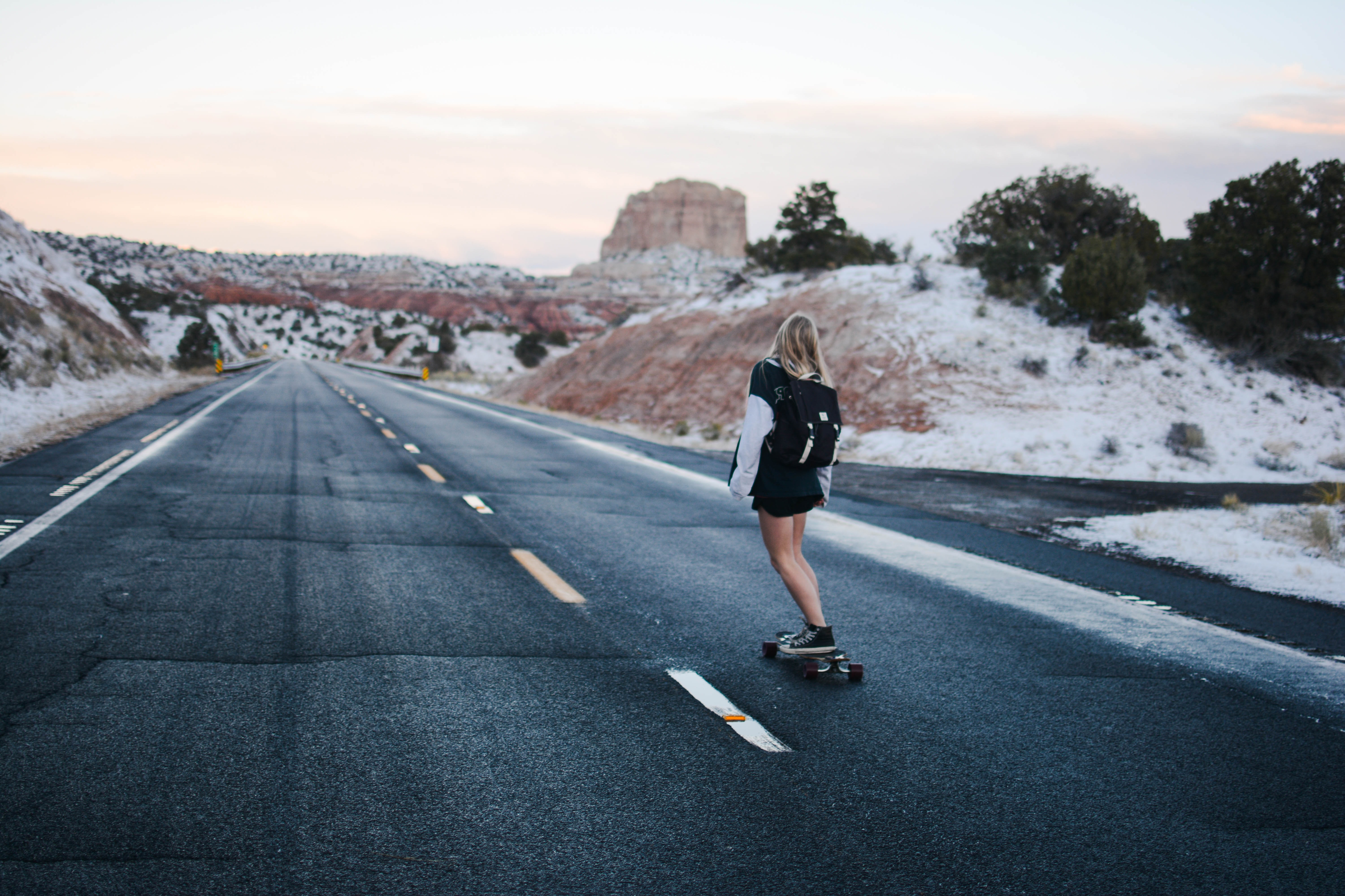A blonde woman wearing an oversized jacket and backpack skateboarding down a desert road in Page