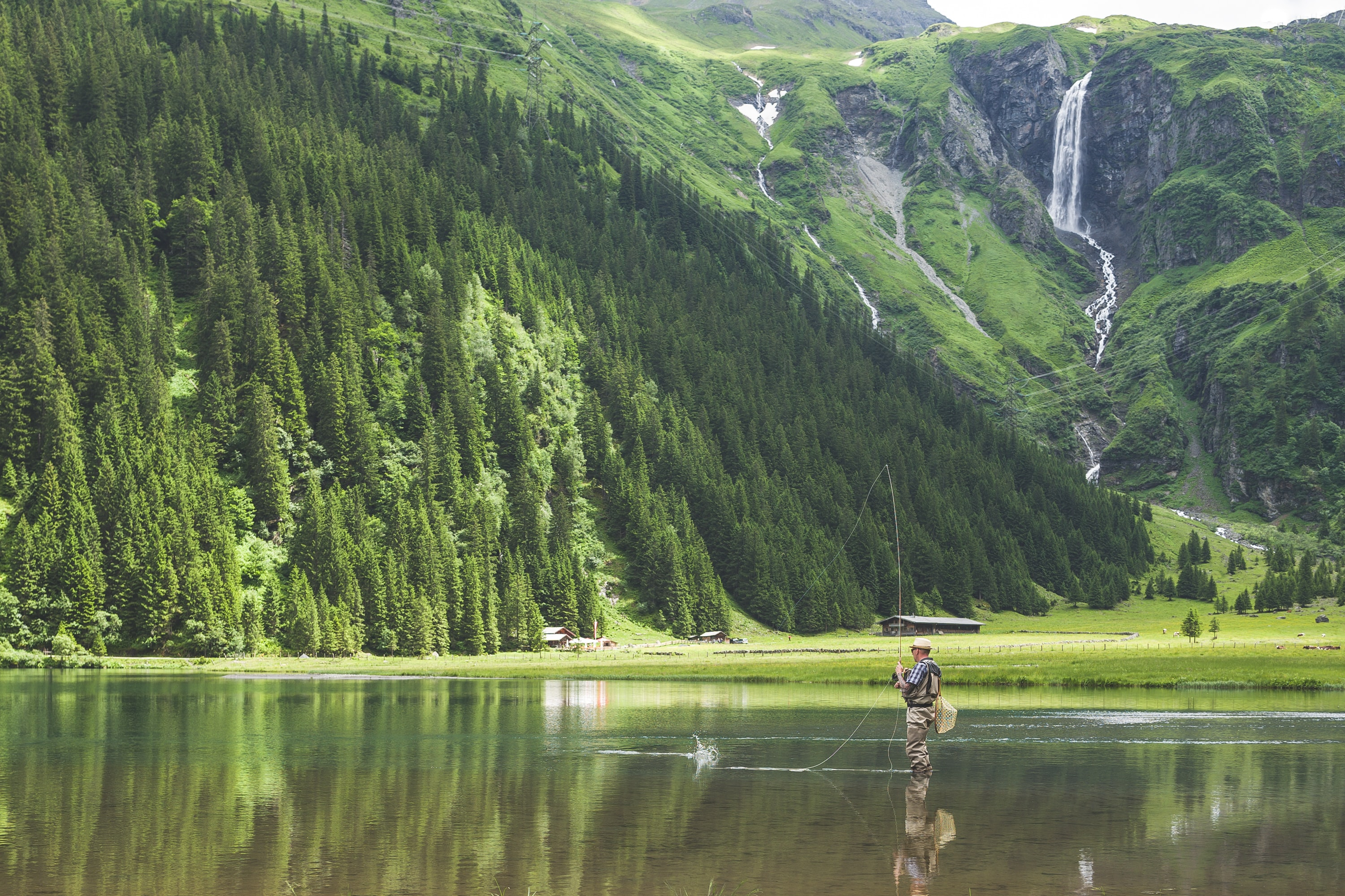 A man fishing while standing in shallow water in a mountain lake