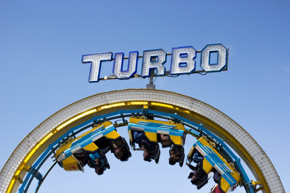 person riding on yellow and blue Turbo roller coaster