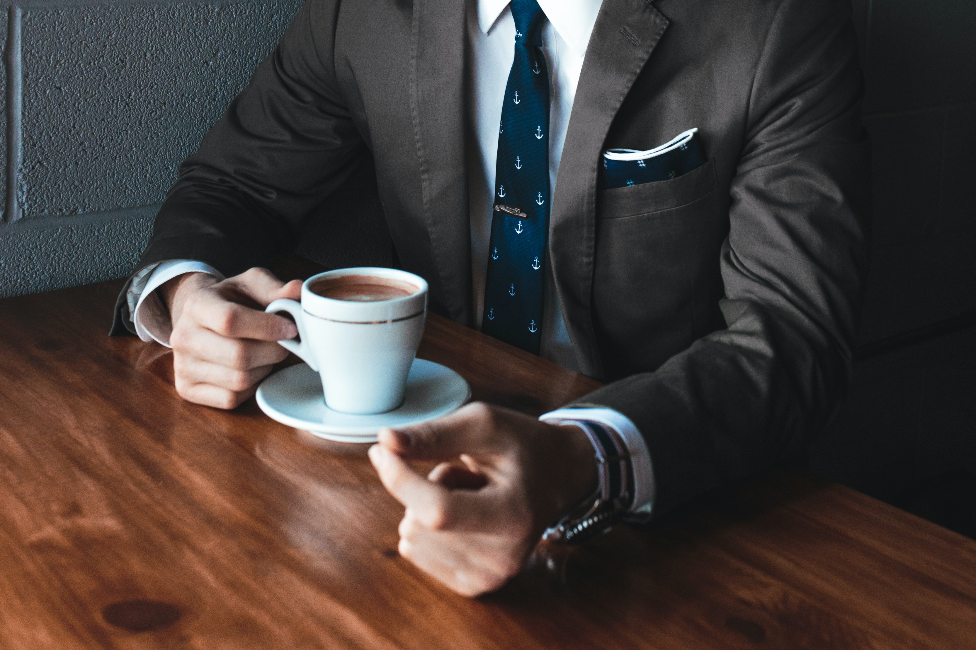 A businessman in a black suit and a tie drinking coffee at a table