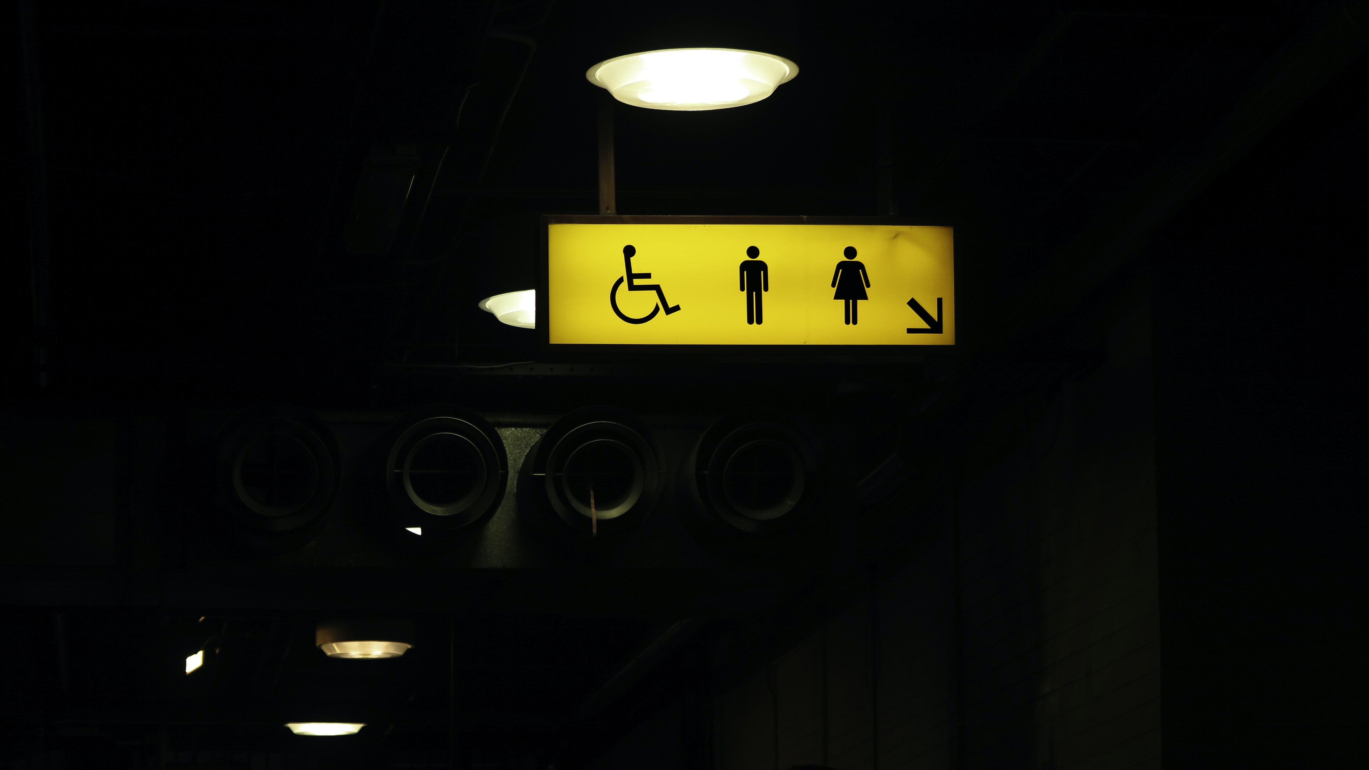 A bright yellow toilet sign in a dark room