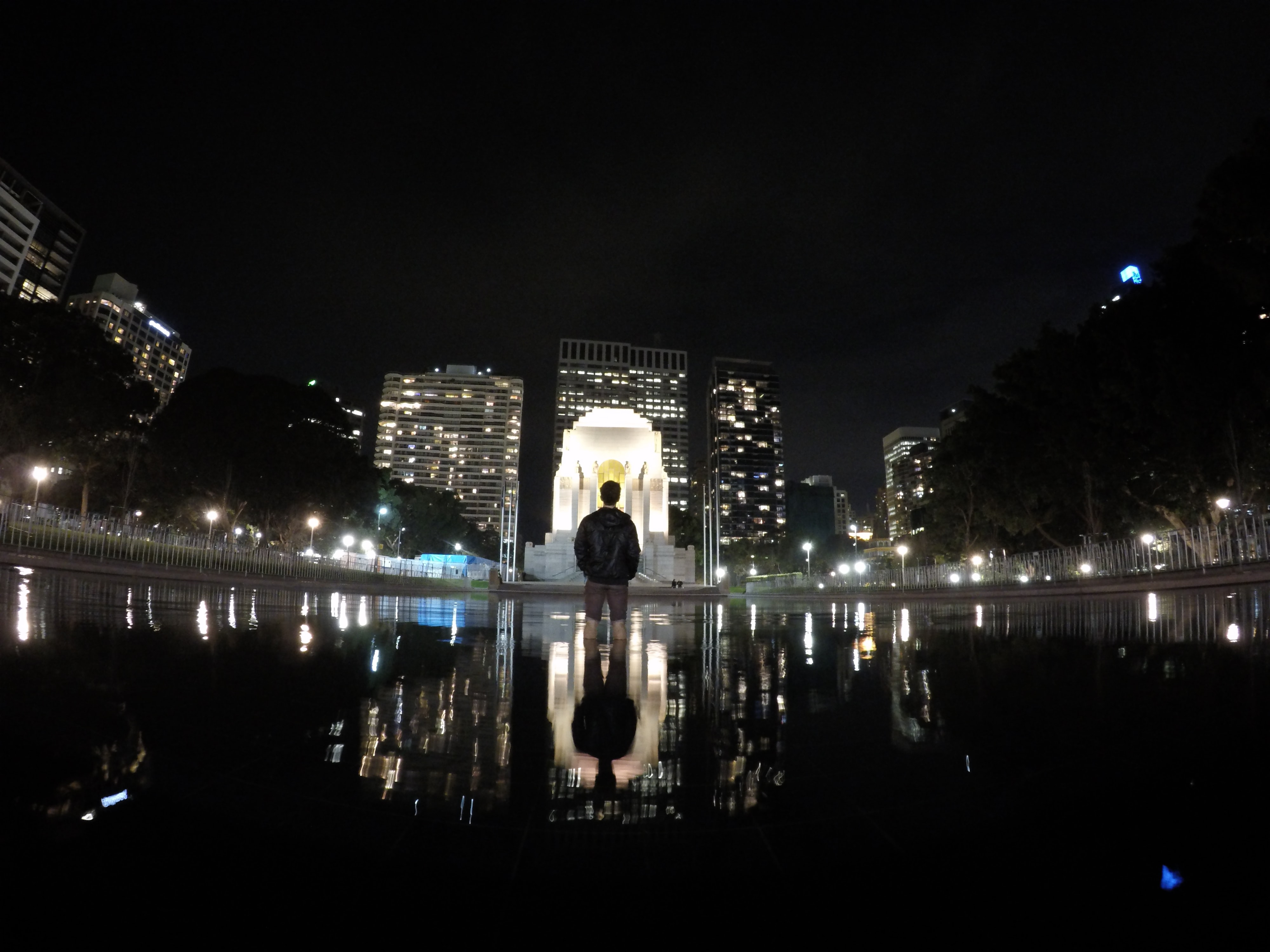 A man wearing a backpack and standing inside a city fountain.