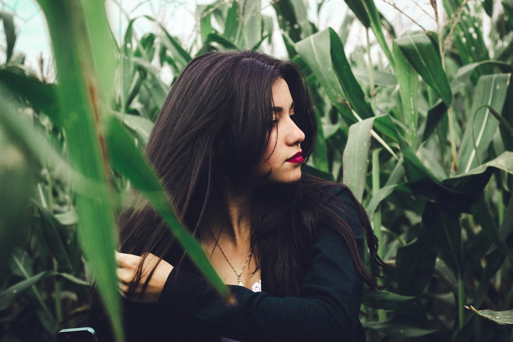 woman wearing black long-sleeved top in cornfield at daytime