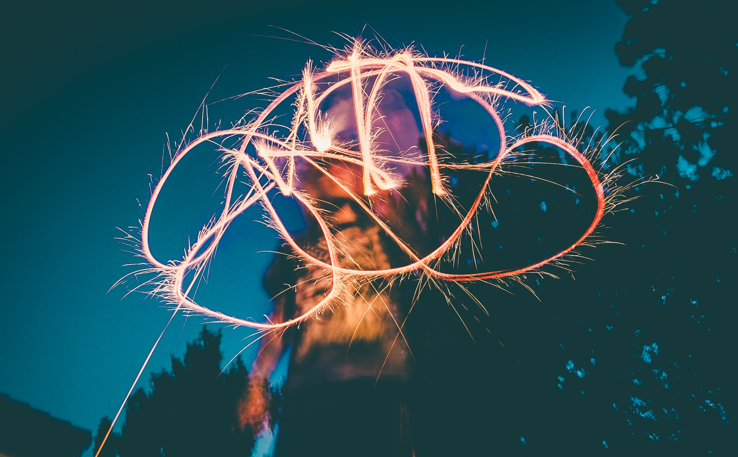 A person draws an abstract pattern in the air with a lighted sparkler firework