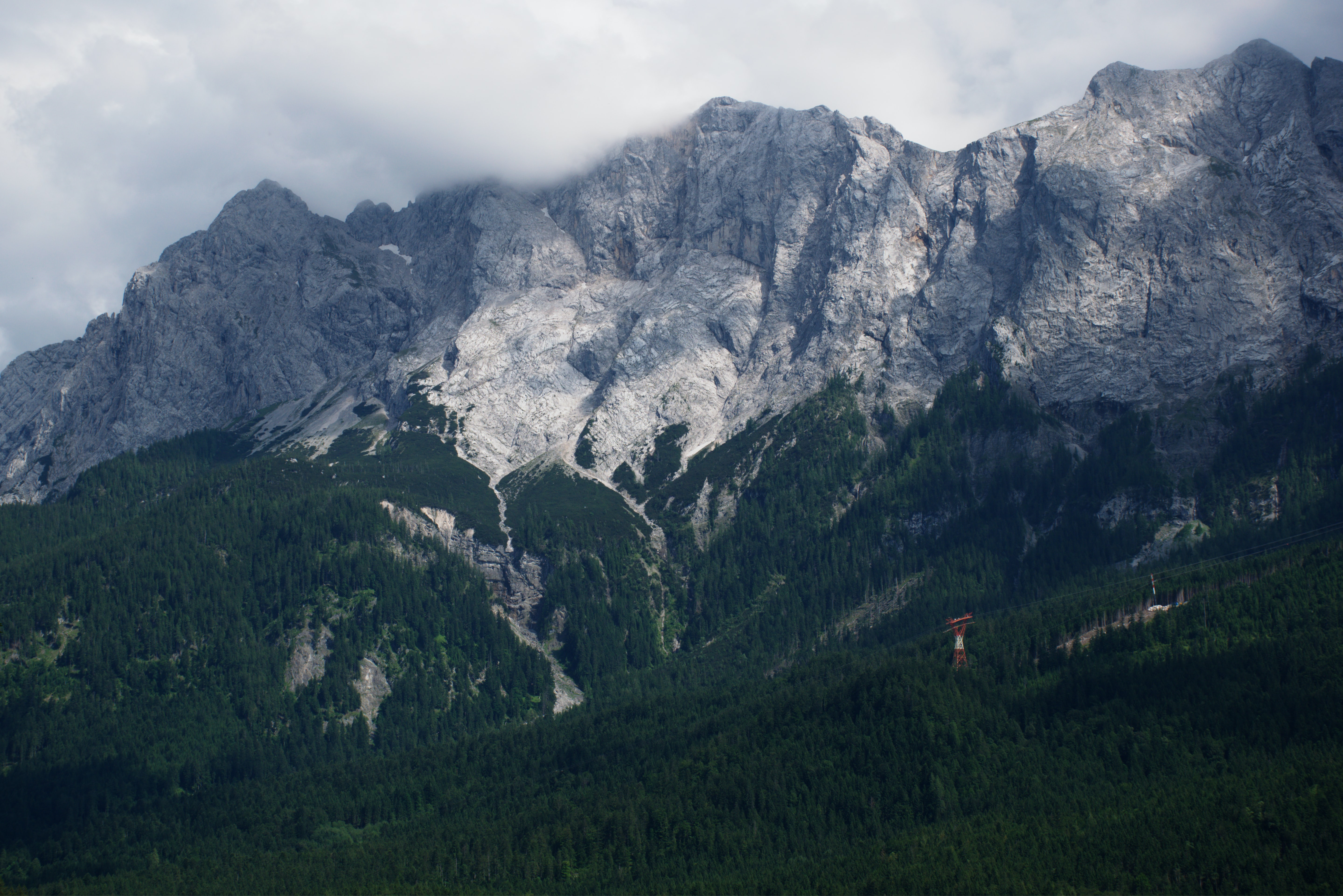 Rugged mountains with wooded hills at their foot