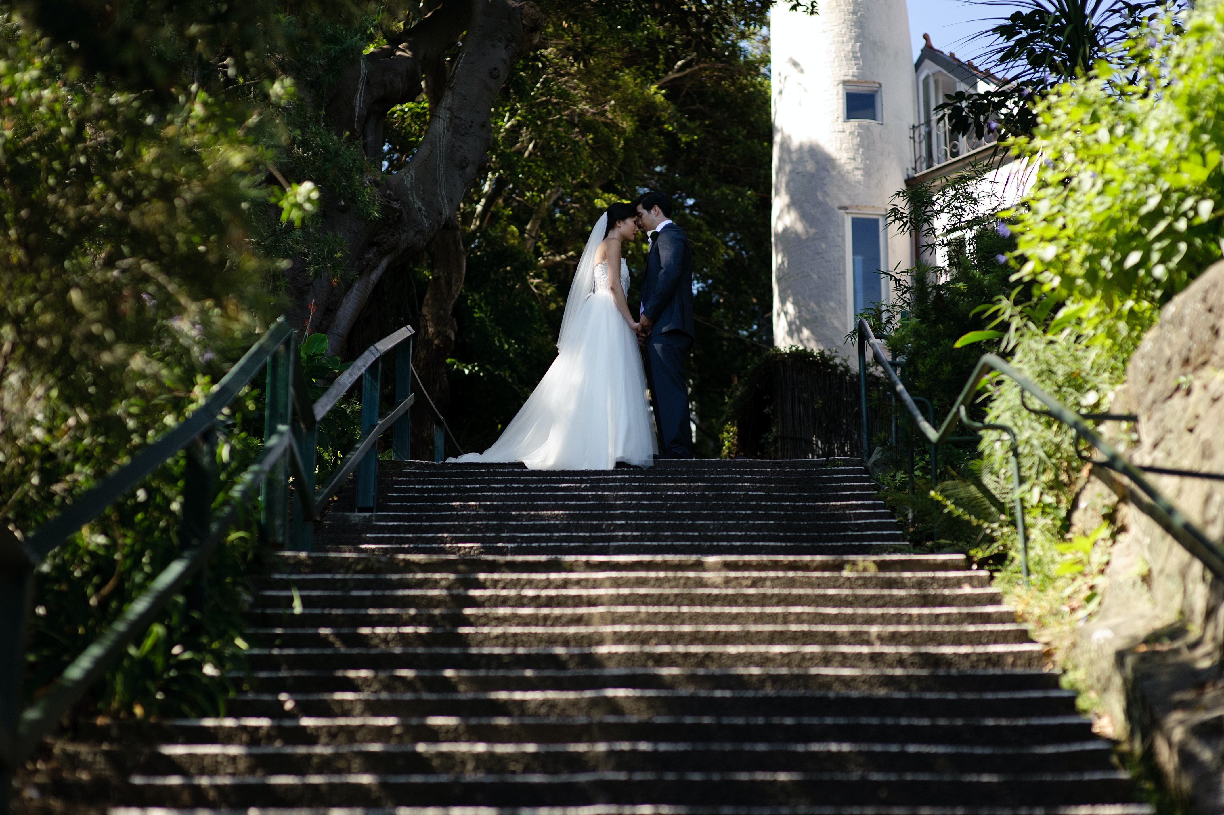 A newlywed couple sharing an intimate moment atop a flight of stairs at Gold Coast