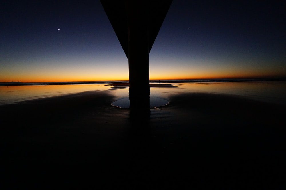 The sun-kissed horizon looms behind the pillar and across the water at dusk at New Brighton