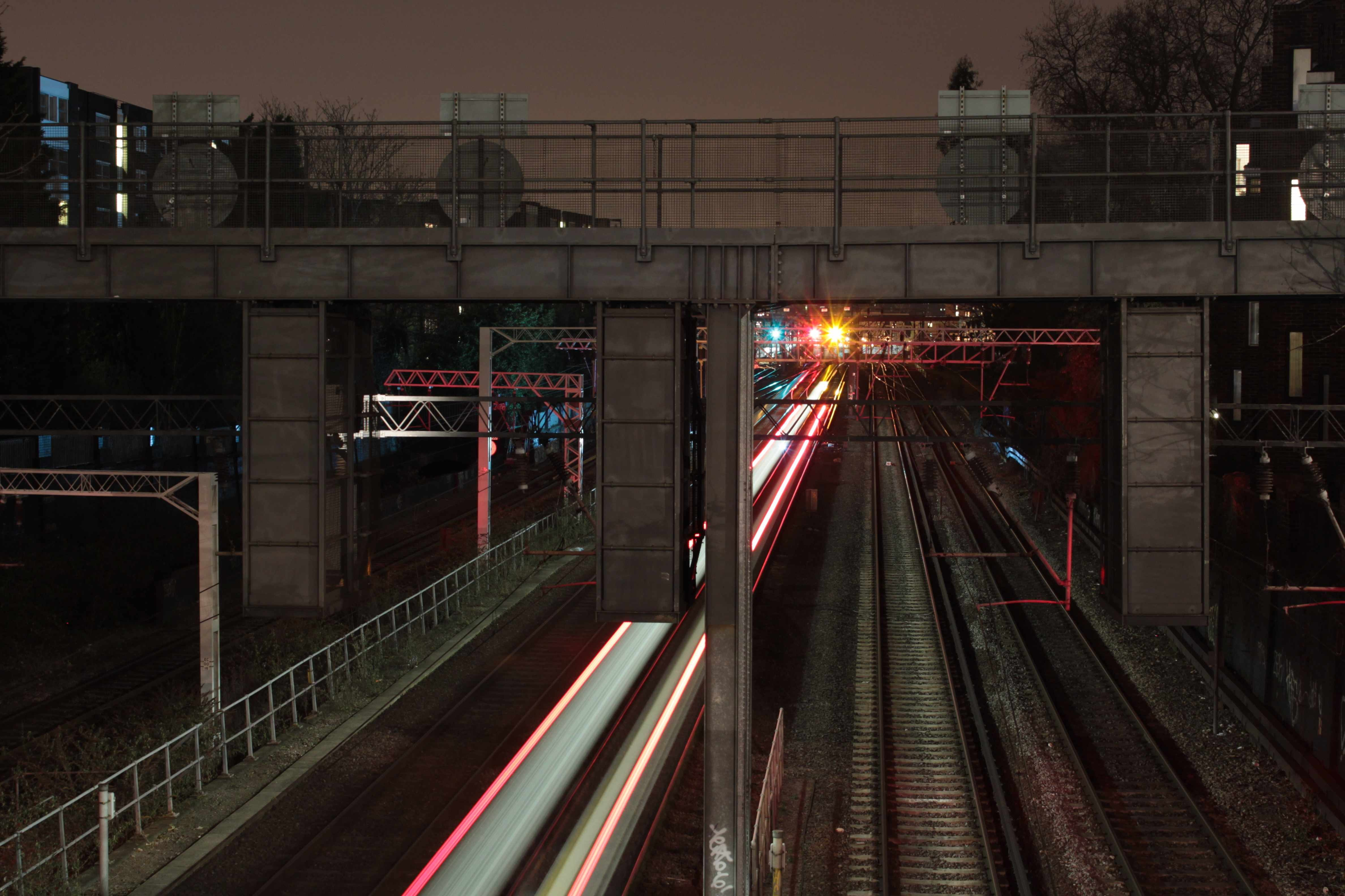 A long-exposure shot with light trails on an urban railroad track under an overpass at night