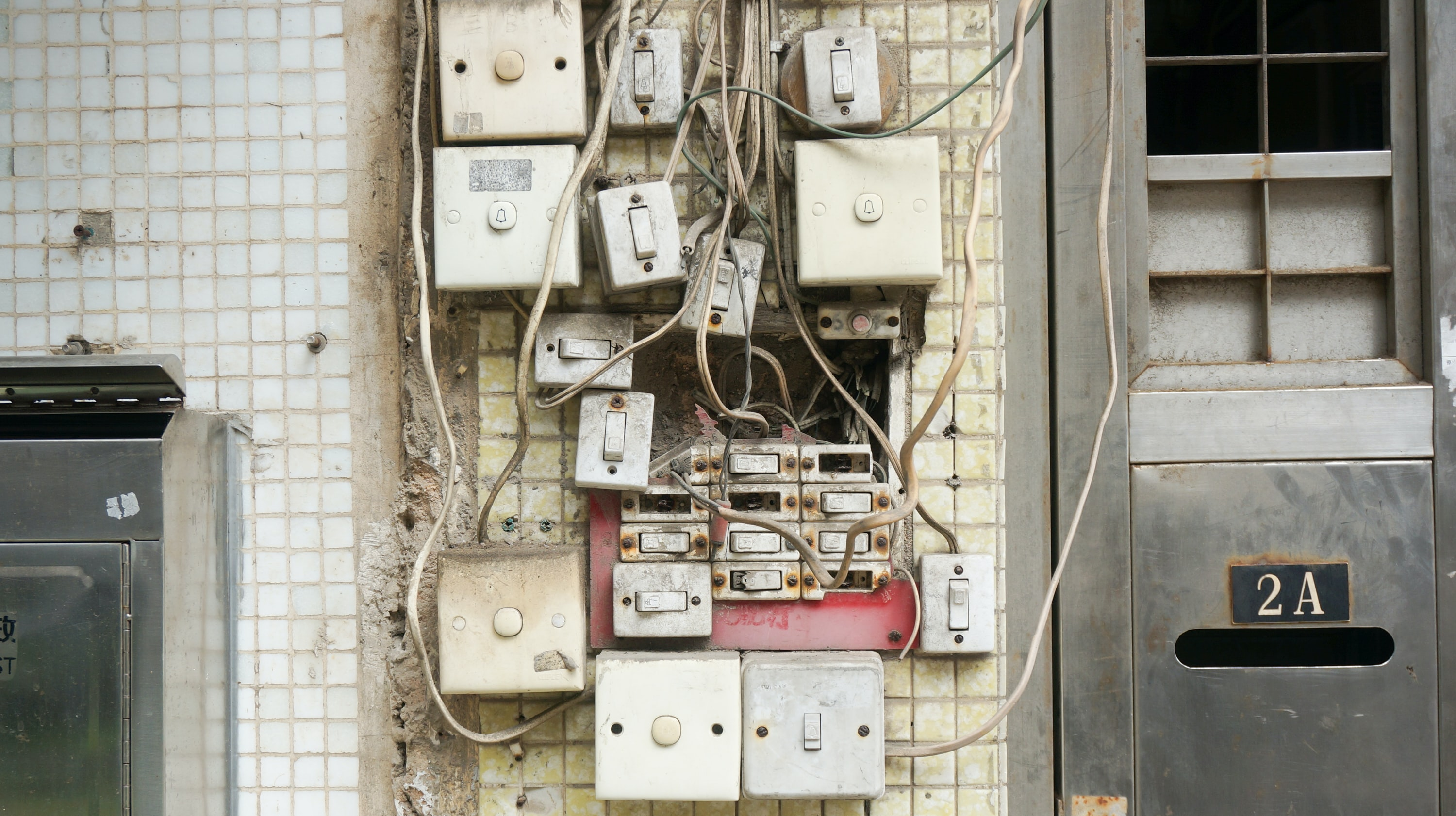 Multiple apartment buzzer switches with exposed wires on a wall.