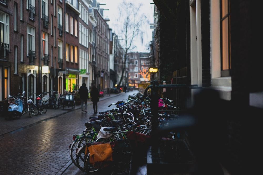 two person walking on road between buildings