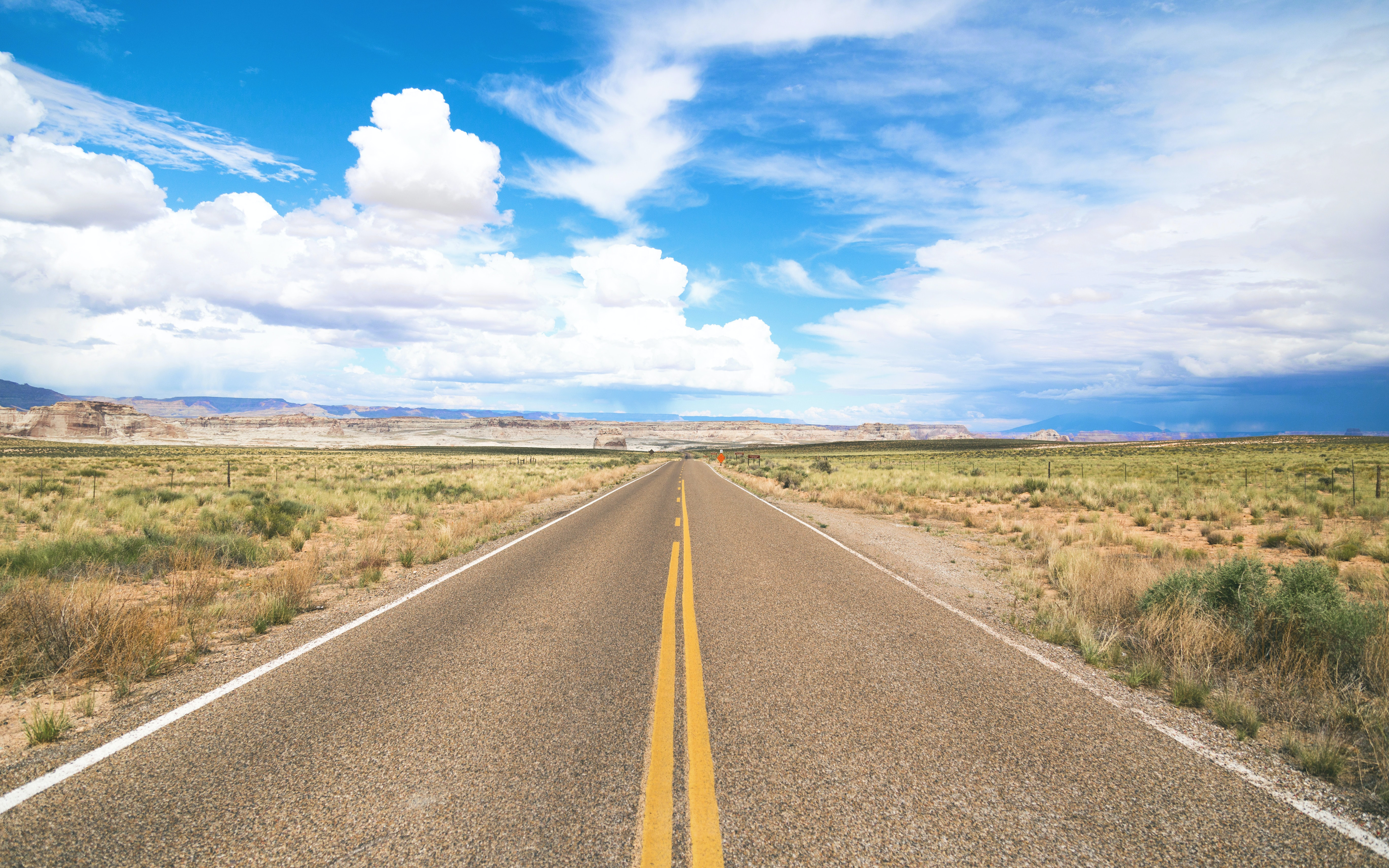 A rural highway surrounded by a desert and meadow with a blue sky filled with fluffy clouds