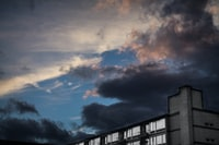 landscape photography of white building under dark cloudy sky