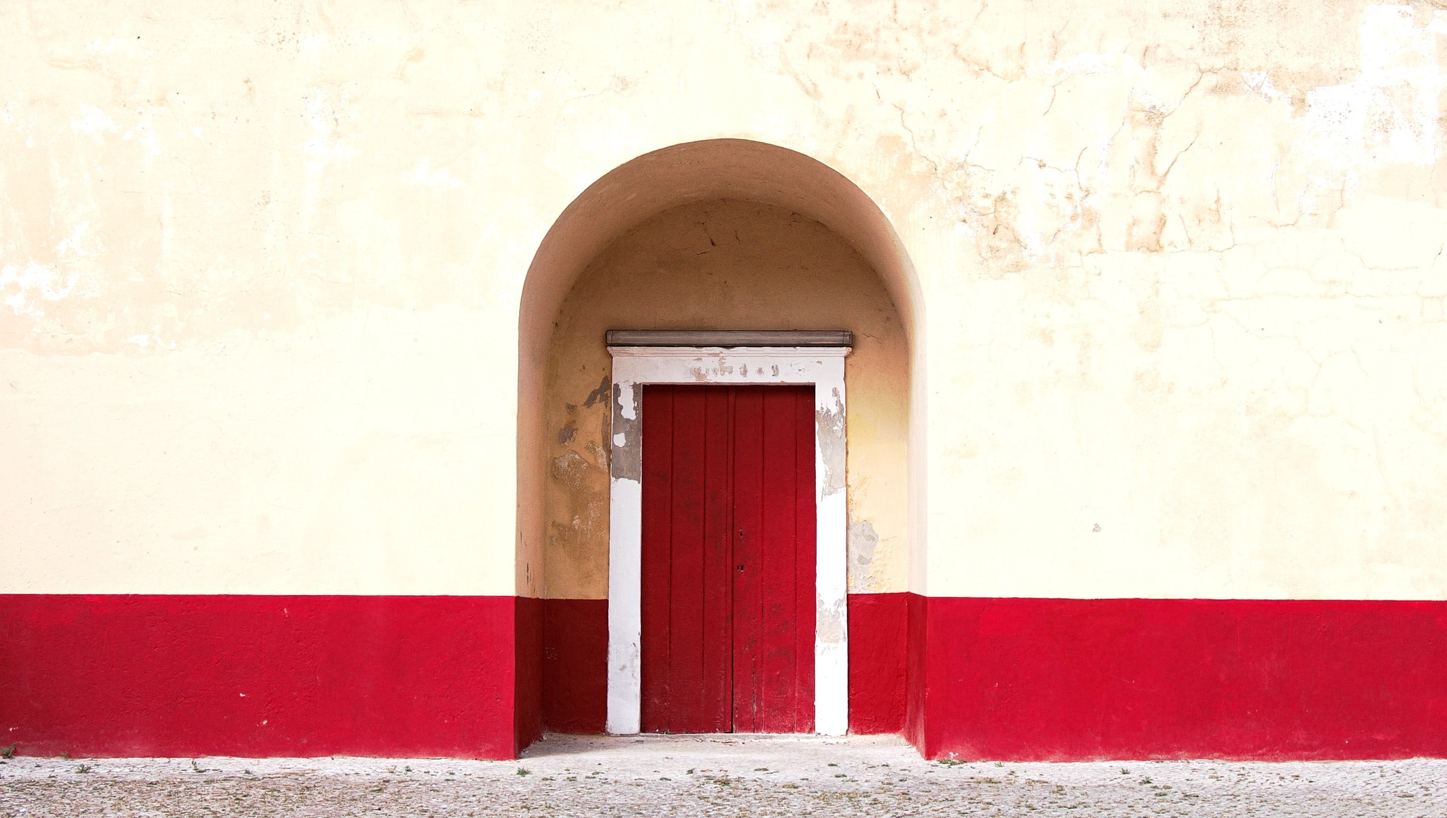 White and red arch door way with a stone walkway outside the door
