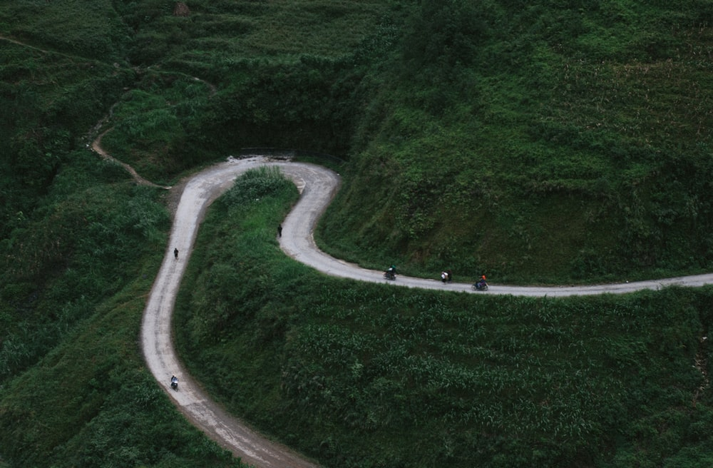 aerial view of curved road beside mountains during daytime