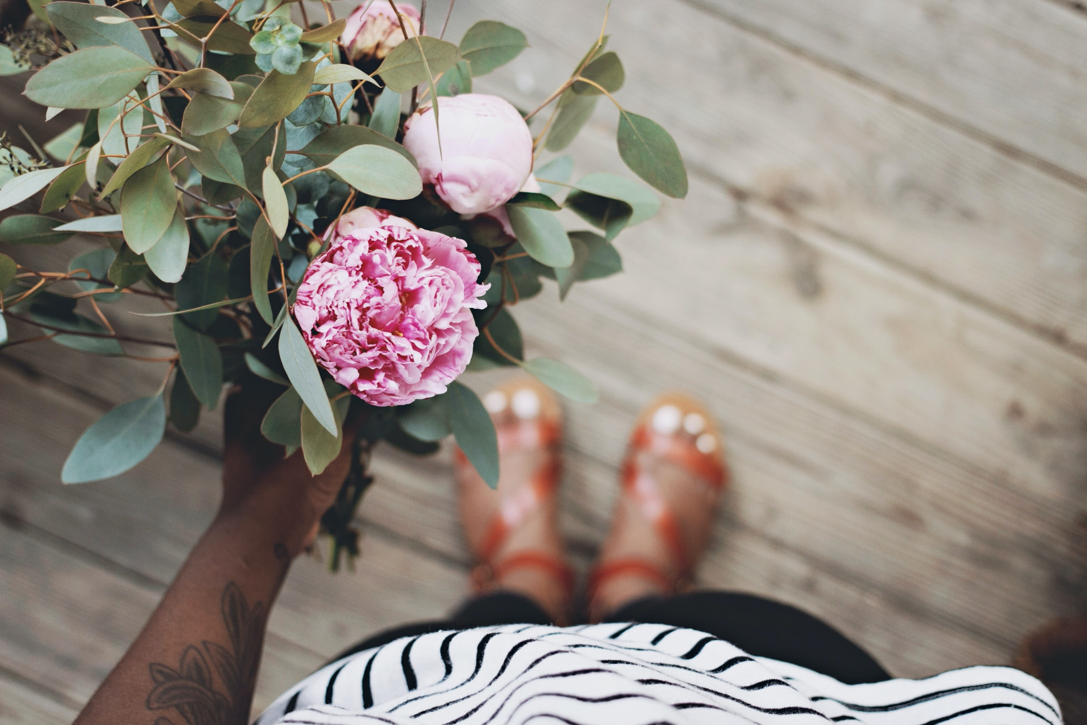 Woman with flower tattoos and sandals holding a bouquet of flowers while standing on wooden floor
