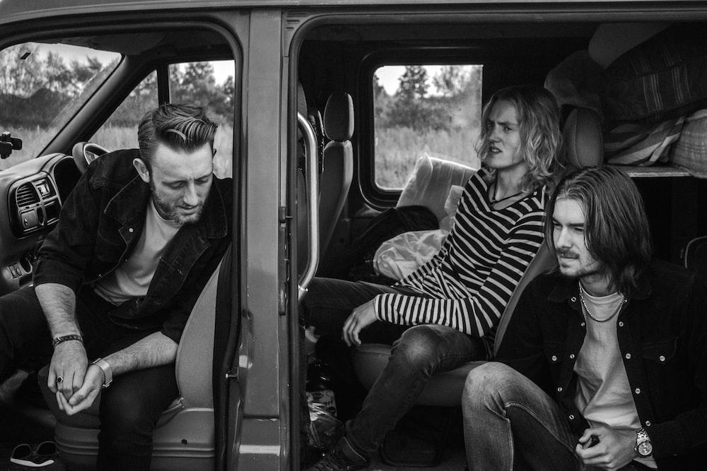 grayscale photo of three men sitting on vehicle seats