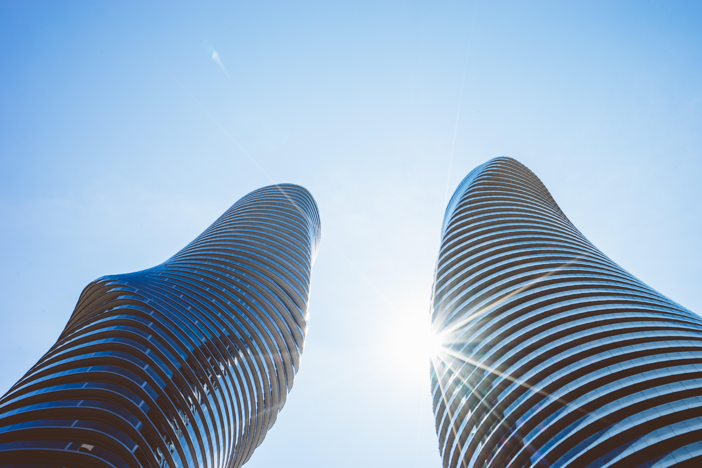 Bright shining sun behind a twin tower skyscraper