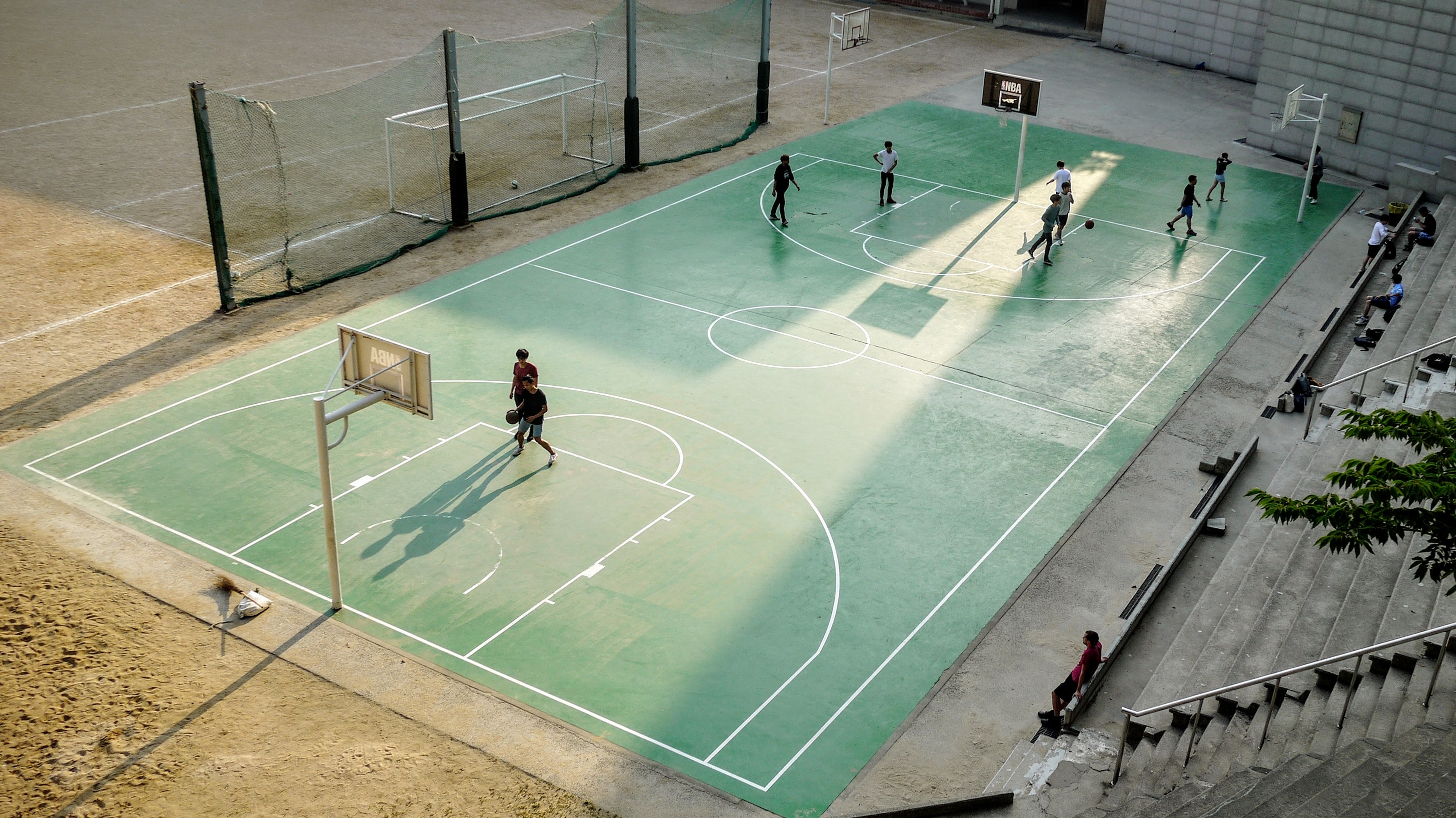 People playing basketball on a green basketball court with bleachers