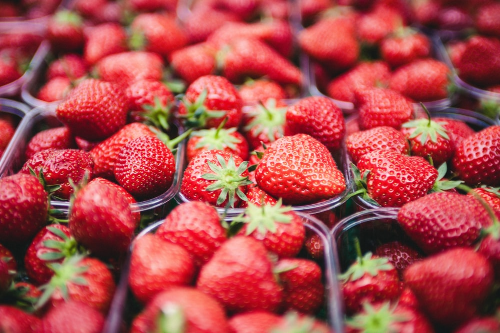 selective focus photo of strawberries in clear plastic containers