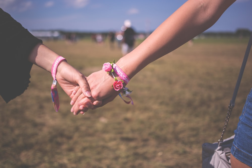 two person holding each other hands