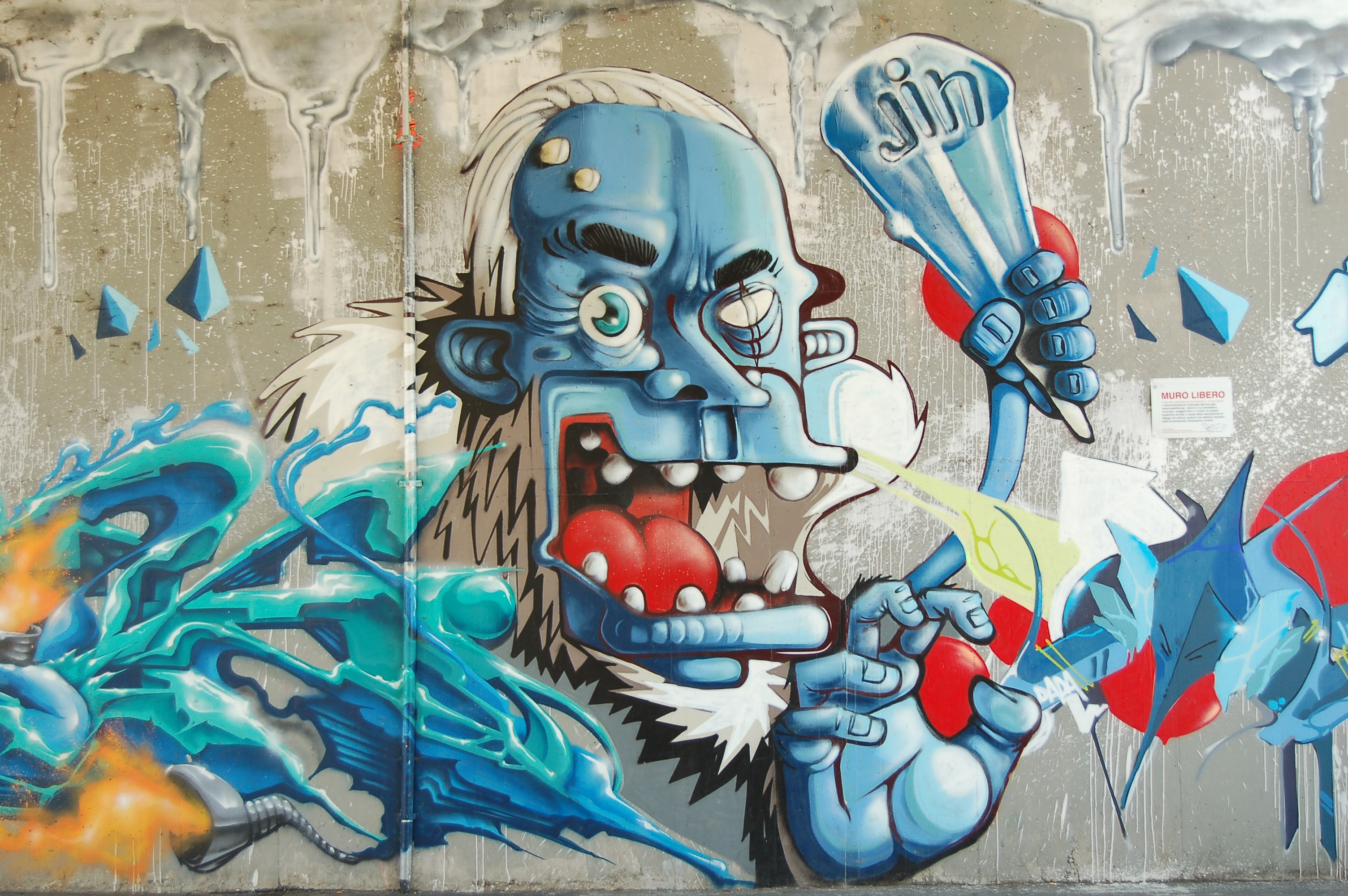 A freaky blue guy holding ice cream, painted on a wall mural.