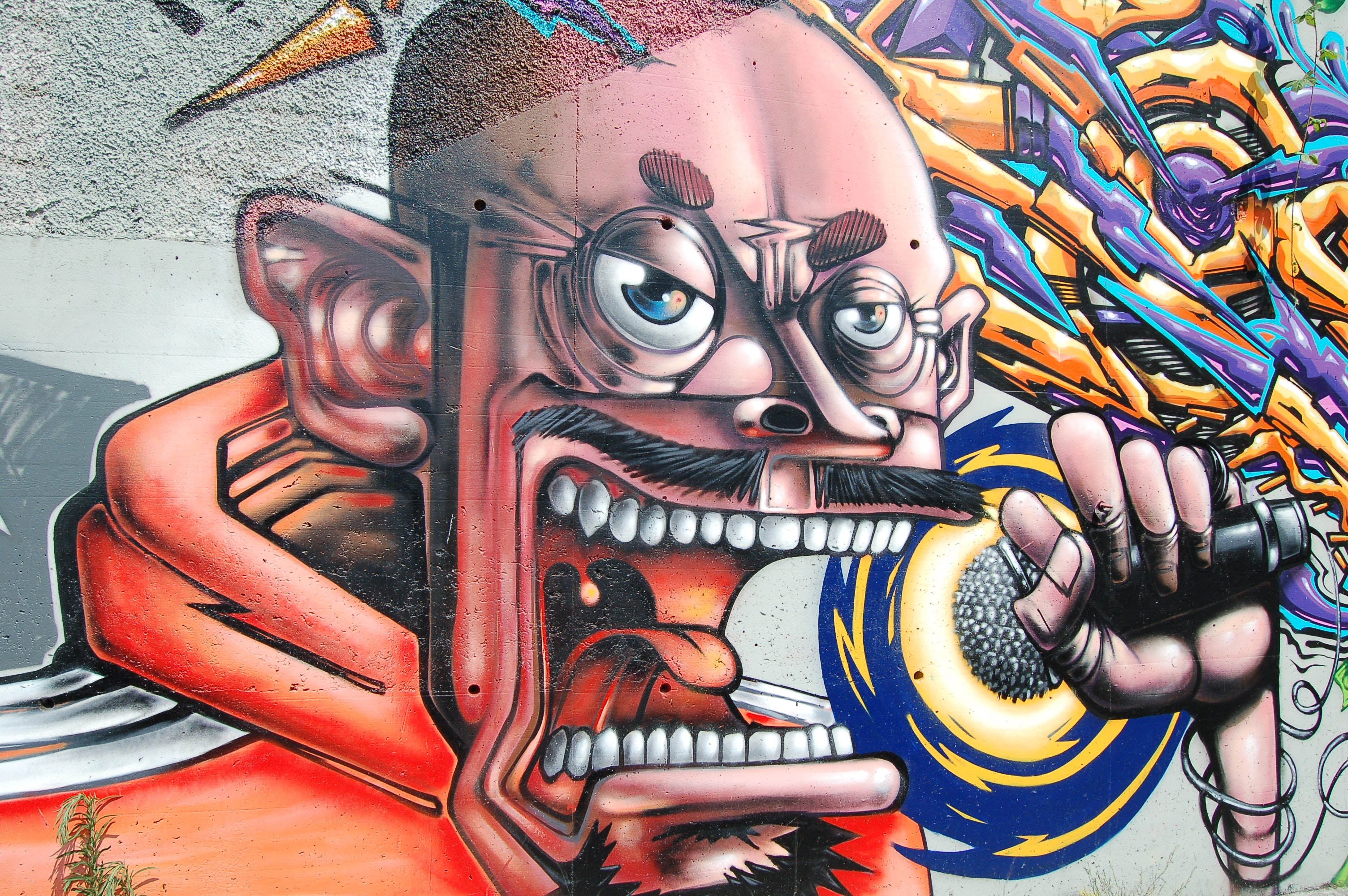 A wall painting of a cartoon middle-age male holding a microphone.