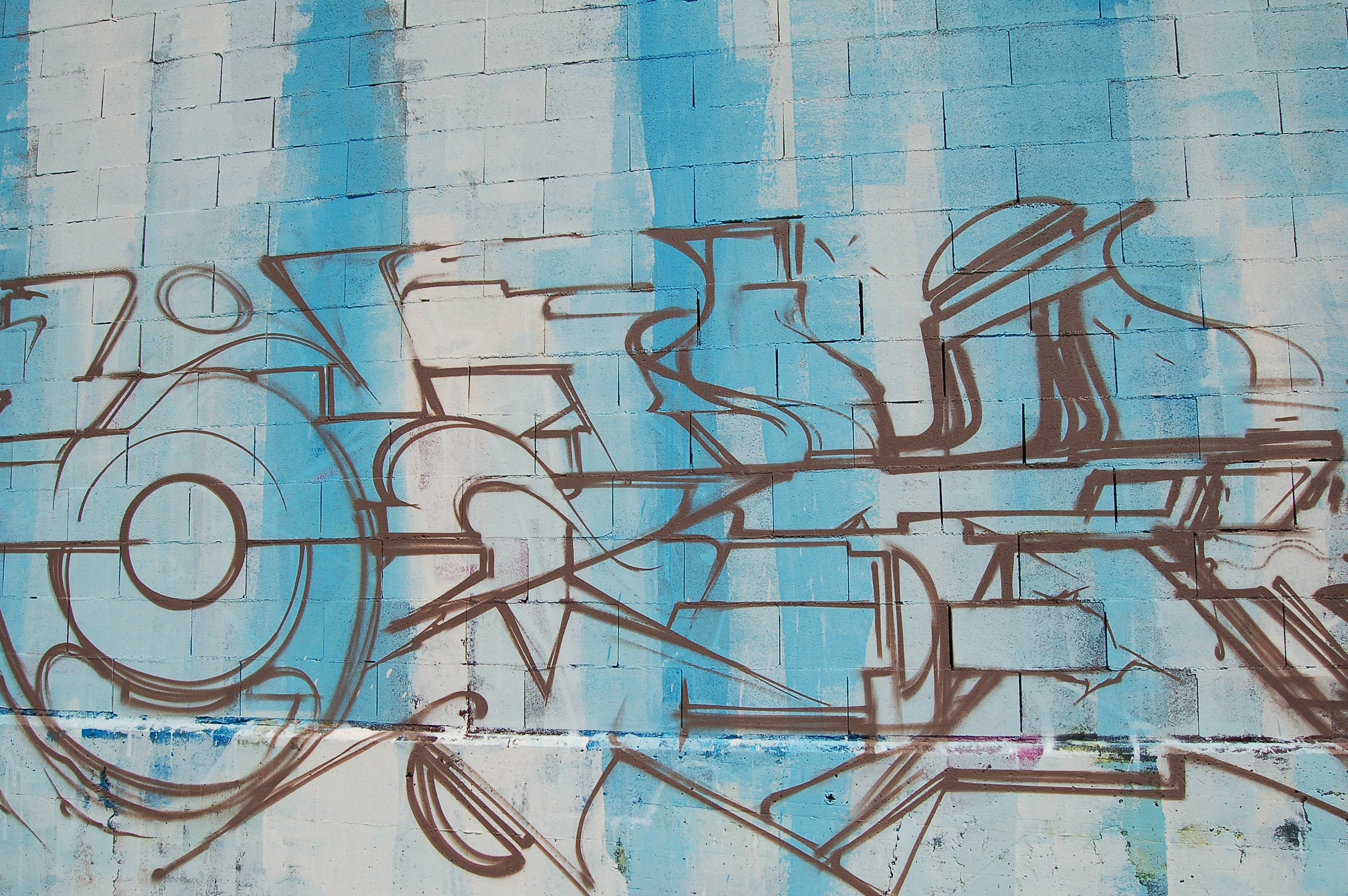A basic graffiti drawing on a blue and white brick wall.